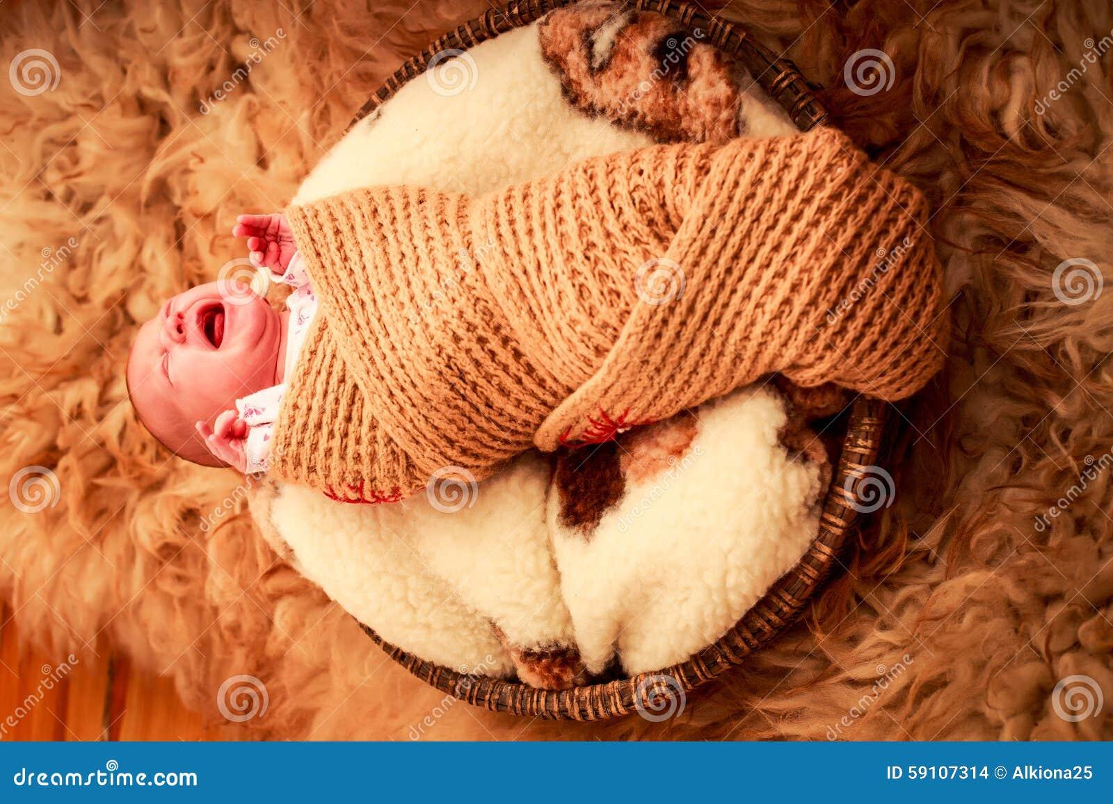 在被编织的围巾啼声盖的新出生的婴孩