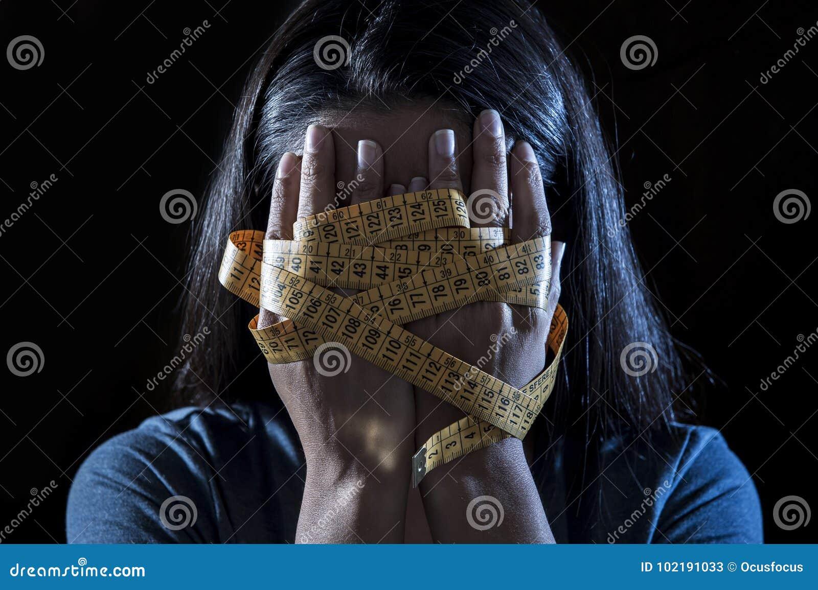 在裁缝措施磁带年轻人沮丧的和担心的女孩遭受的厌食或善饥癖营养dis的覆盖物面孔包裹的手