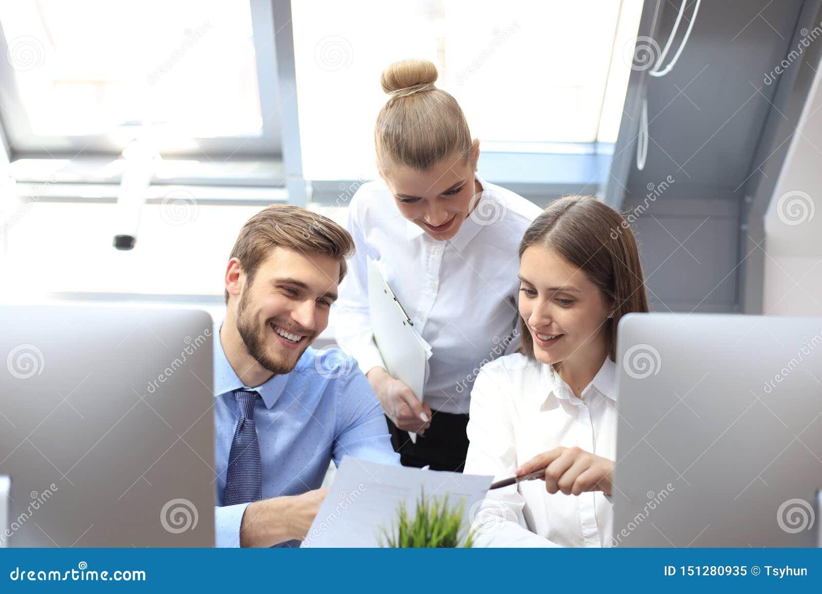 在见面的起始的企业队在现代明亮的办公室内部激发灵感,研究片剂和个人计算机计算机