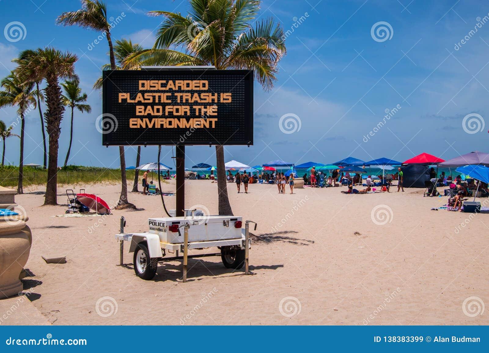 在说的海滩的流动标志,被放弃的塑料垃圾为环境是坏的