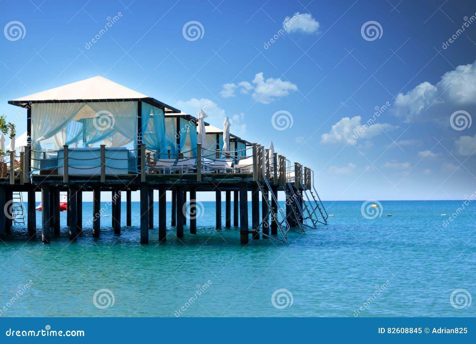 在豪华旅游胜地使与海、天空和机盖的风景靠岸