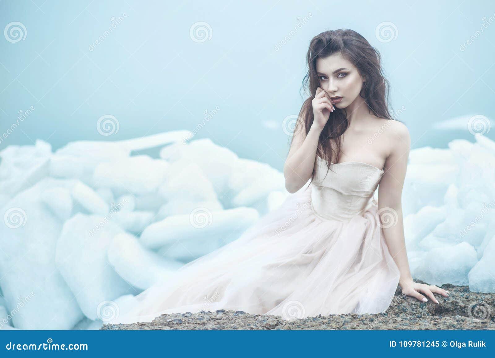 在豪华无背带的束腰舞会礼服的年轻美好的模型坐残破的冰平板在有薄雾的海边
