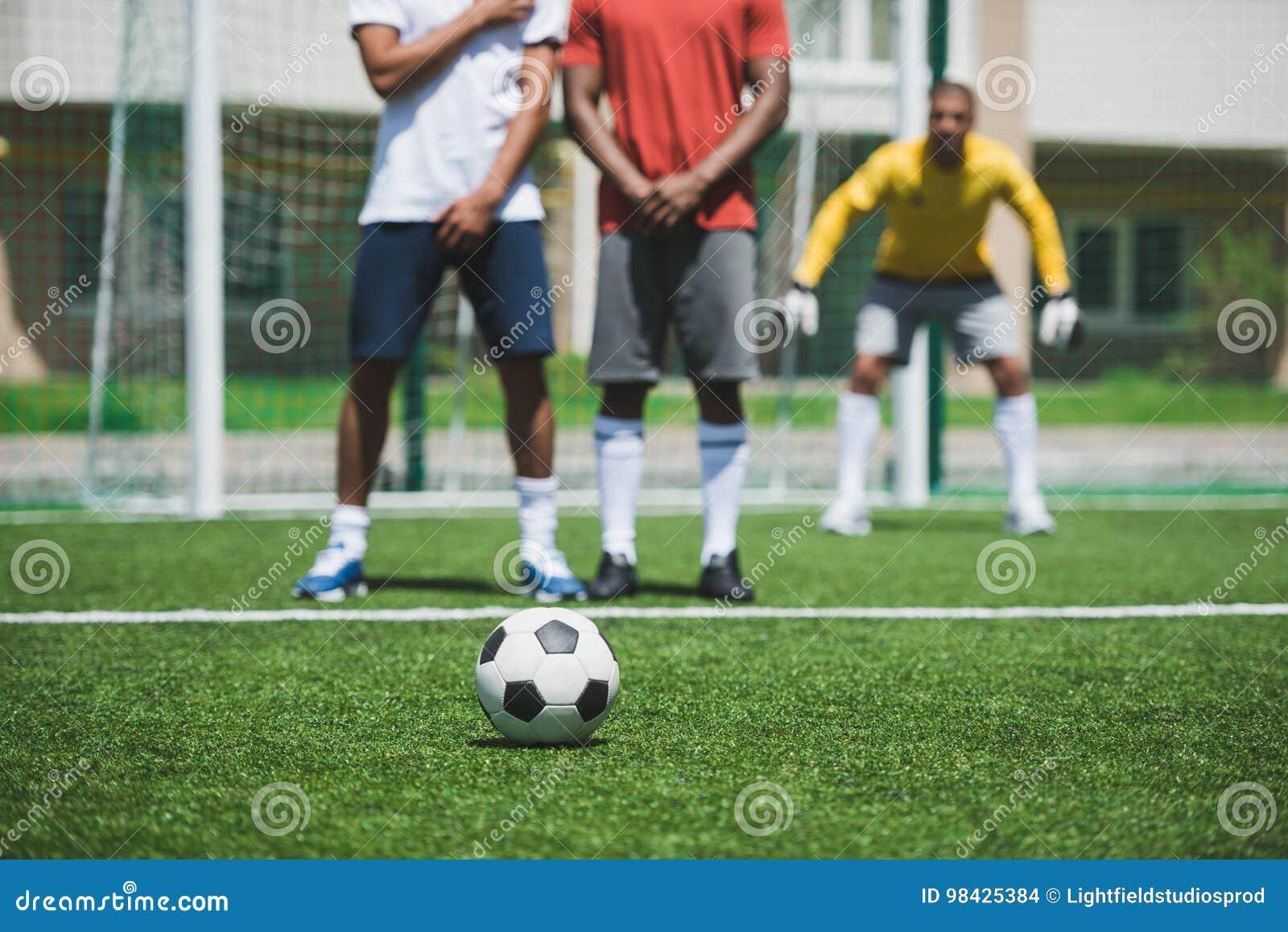 在足球比赛期间的足球运动员在沥青,在前景的焦点