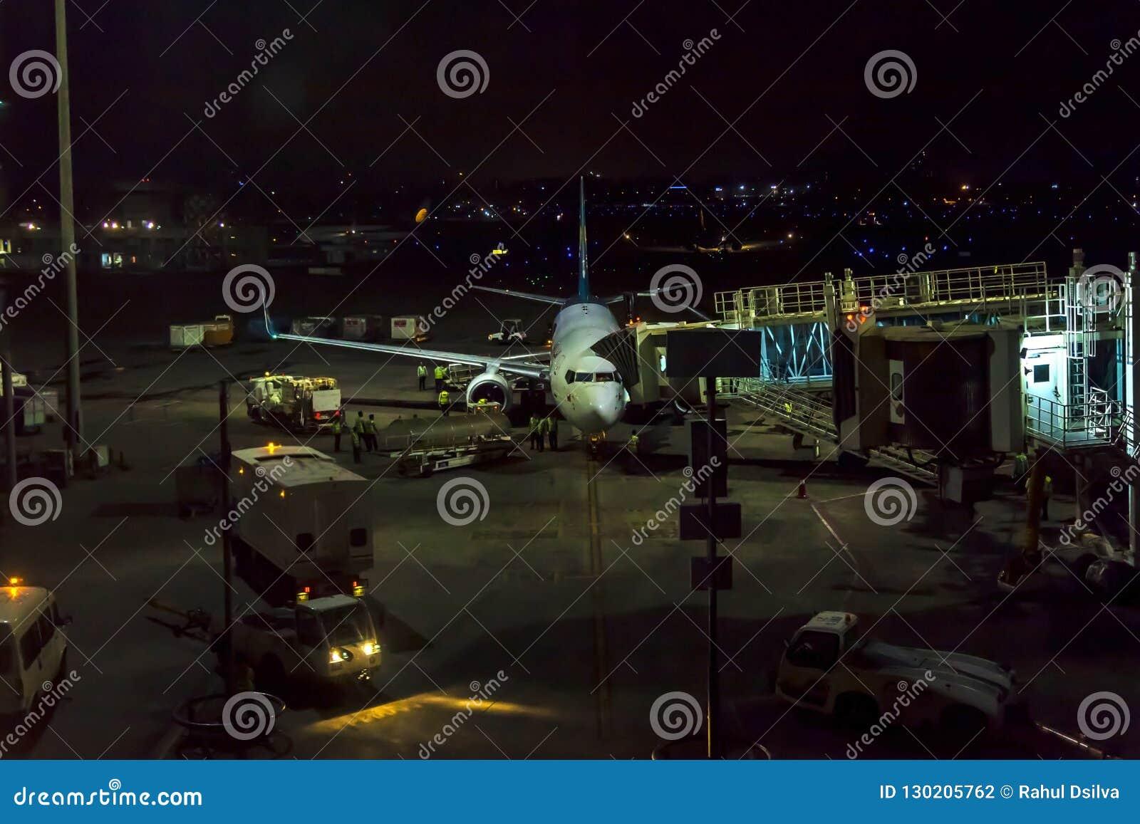 在跑道的乘客飞机在终端附近在夜间的一个机场 机场做乘客的a的土地乘员组飞行服务