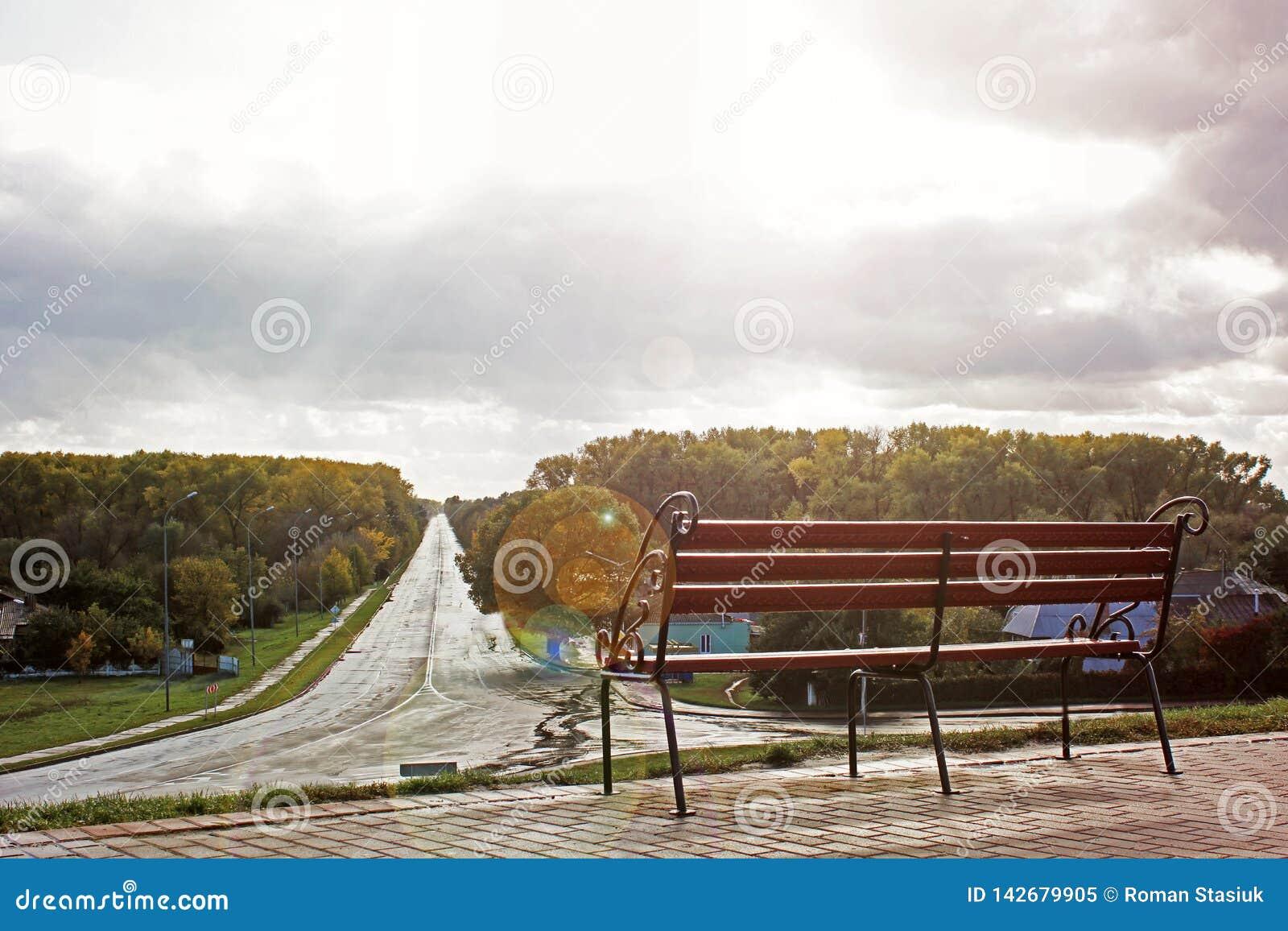 在路的背景的伪造的长凳