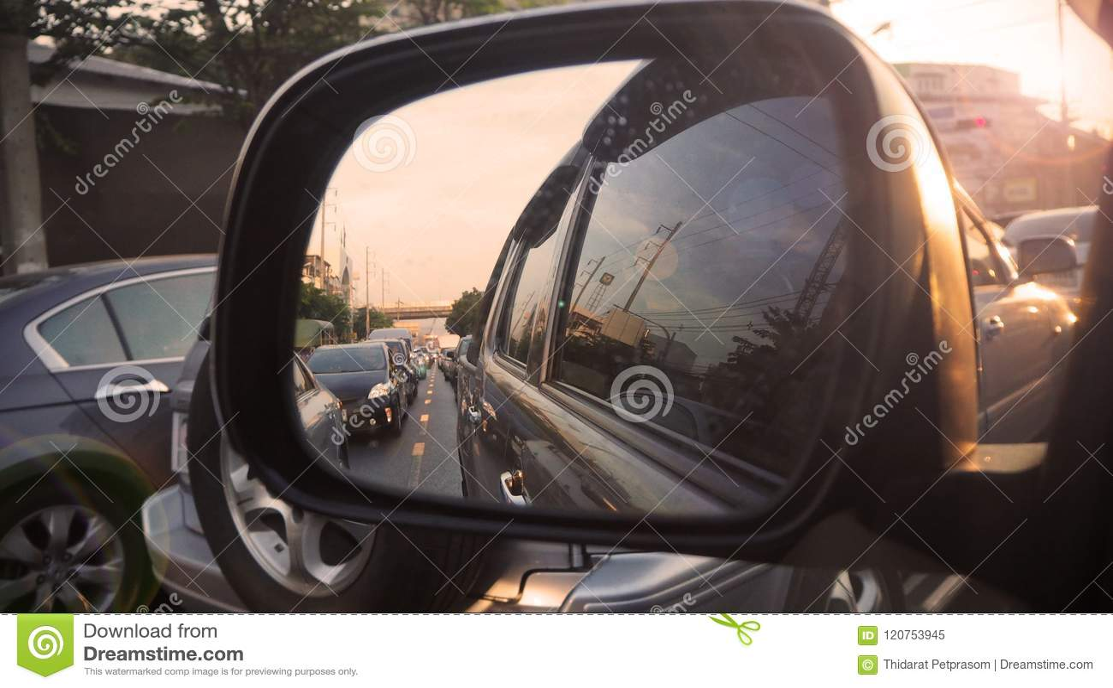 在路视图的交通堵塞通过有后边日落的后视镜汽车