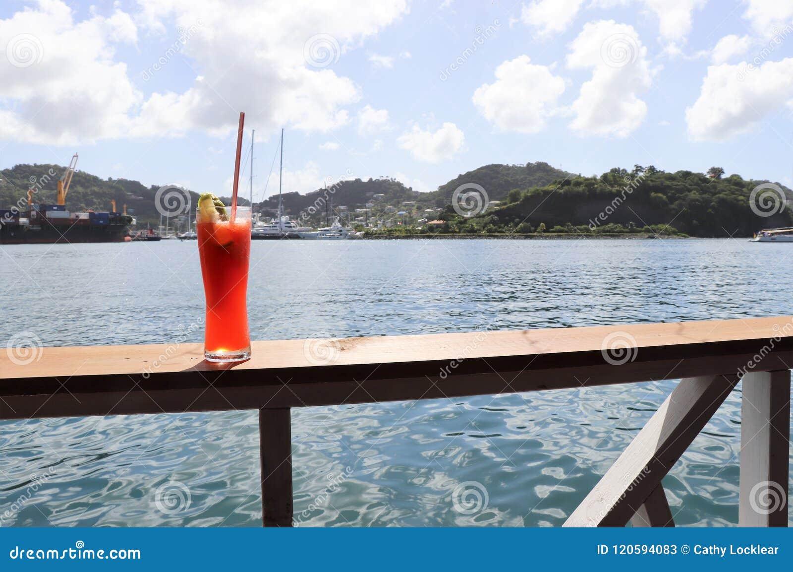 在路轨的冰冷的饮料有海洋的和热带海岛场面在背景中