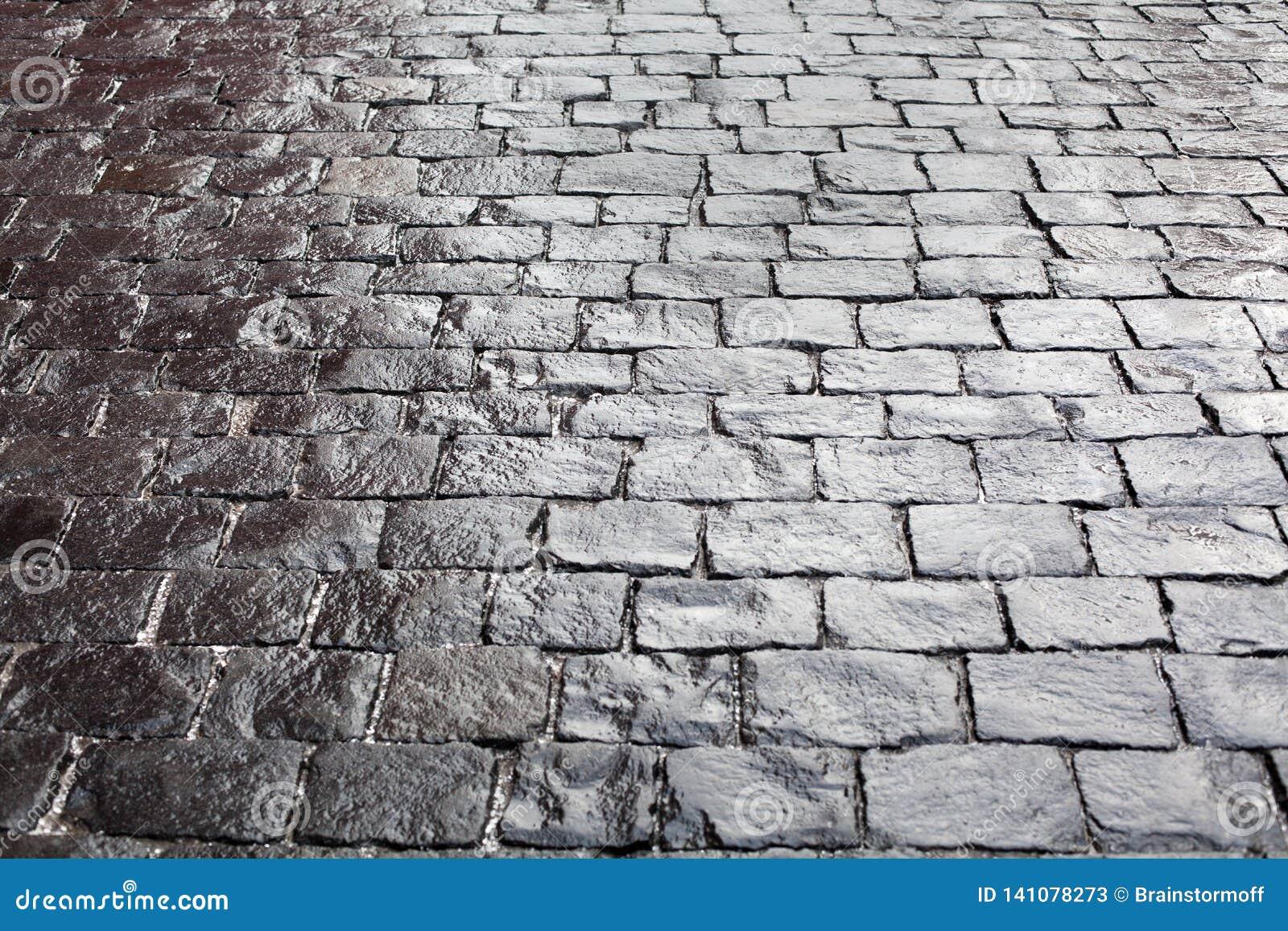 在路面背景、石边路纹理灰色或者黑色,湿砖路面样式顶视图关闭的鹅卵石