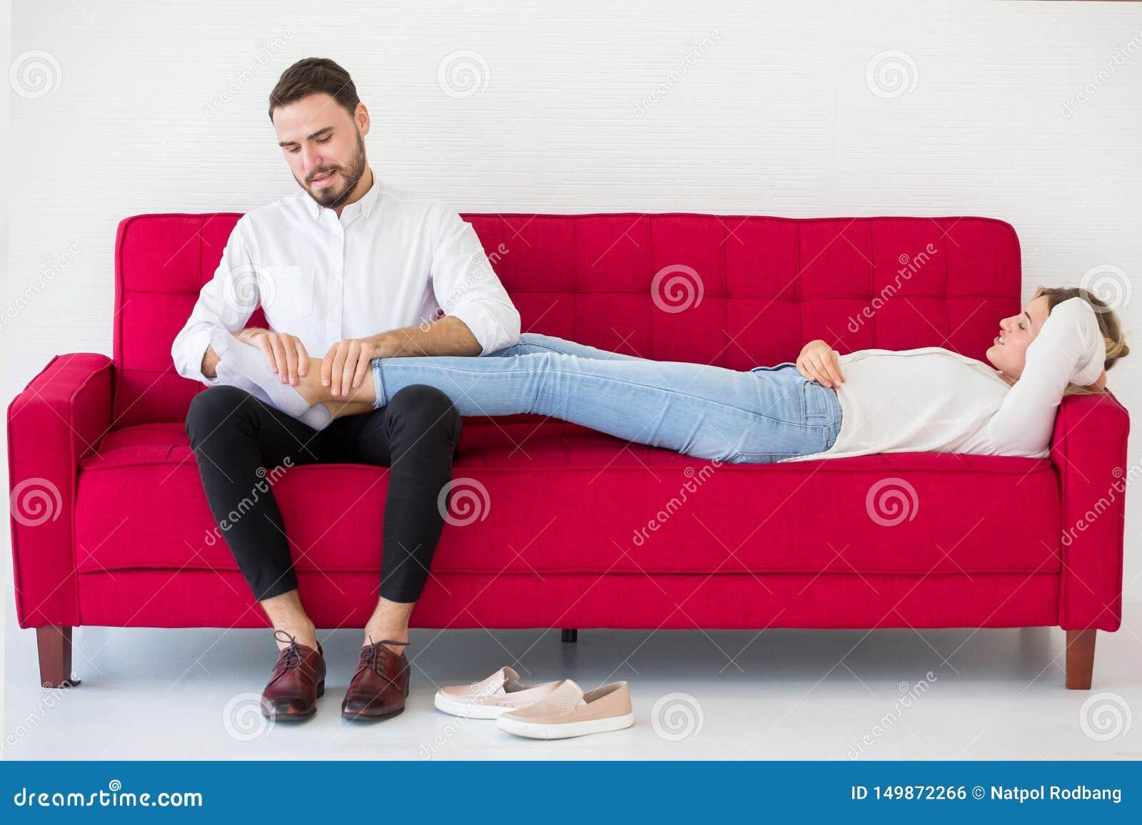 在躺下在红色沙发男朋友的爱女朋友的夫妇在家按摩她的脚,户内
