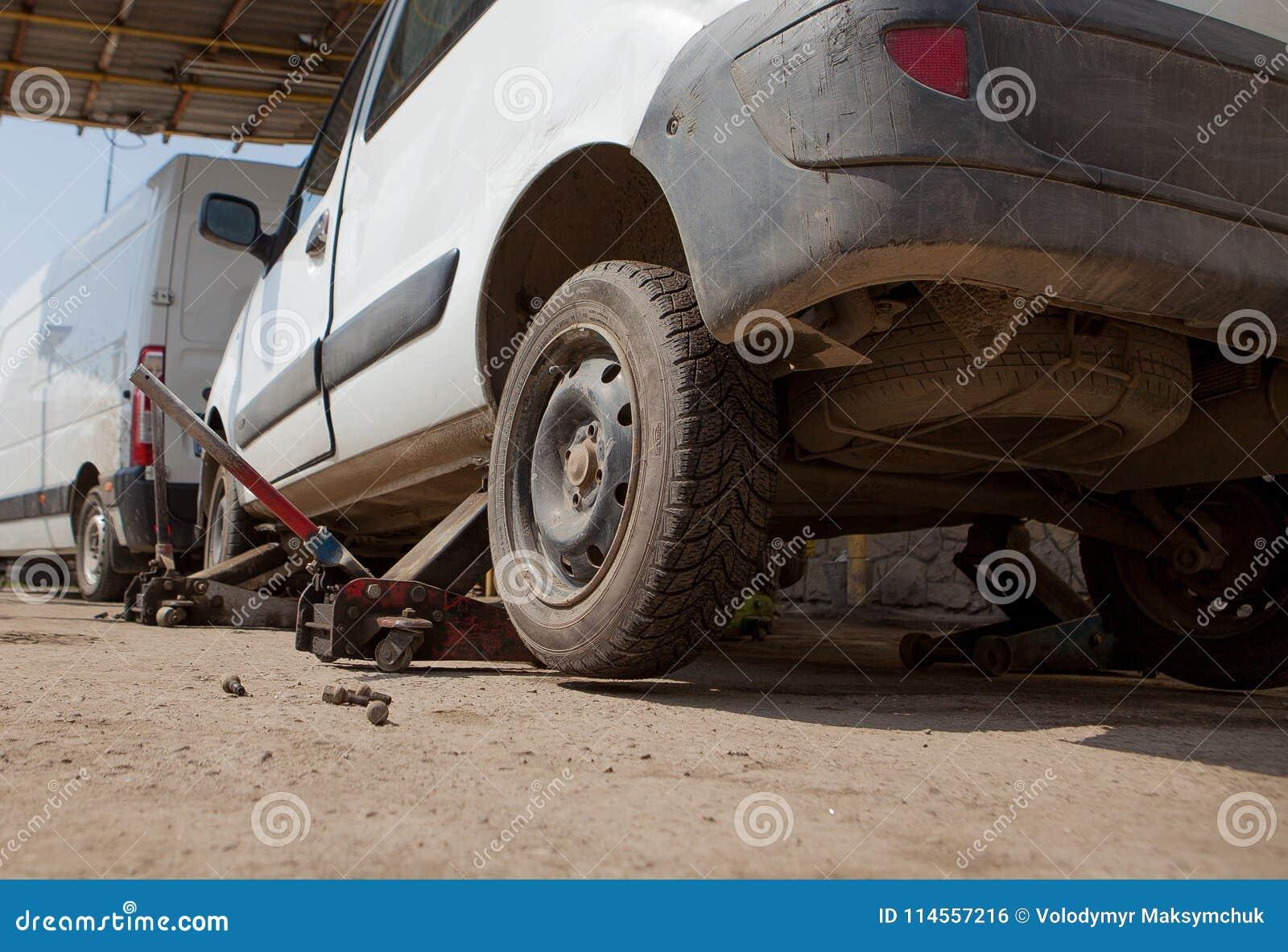 在车库固定的汽车,水力地板用千斤顶压出或拔出器拔出汽车,没有轮胎的轮子