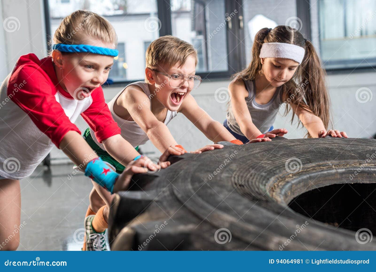 在运动服训练的可爱的孩子与在健身演播室的轮胎