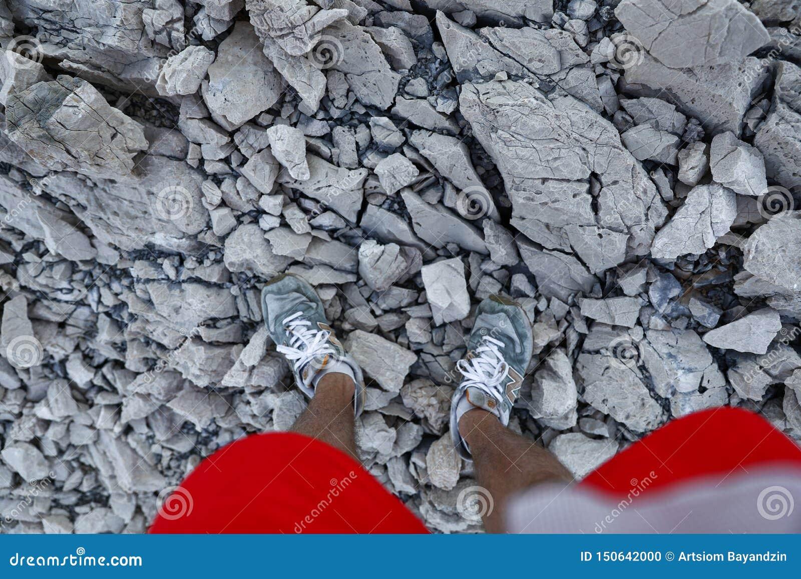 在运动鞋的腿和在岩石道路的红色短裤在山