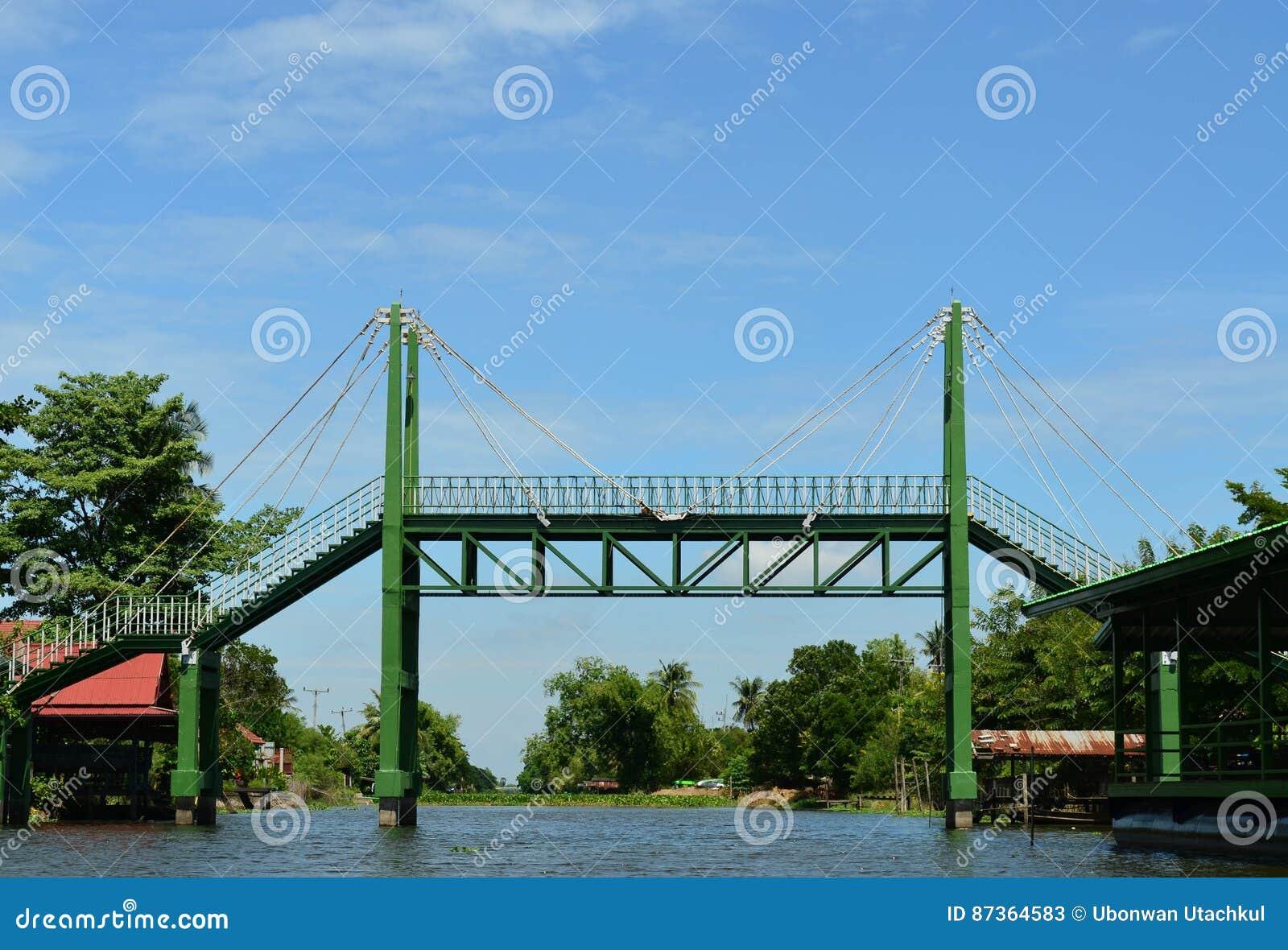 在运河和蓝天的绿色吊索铁桥梁