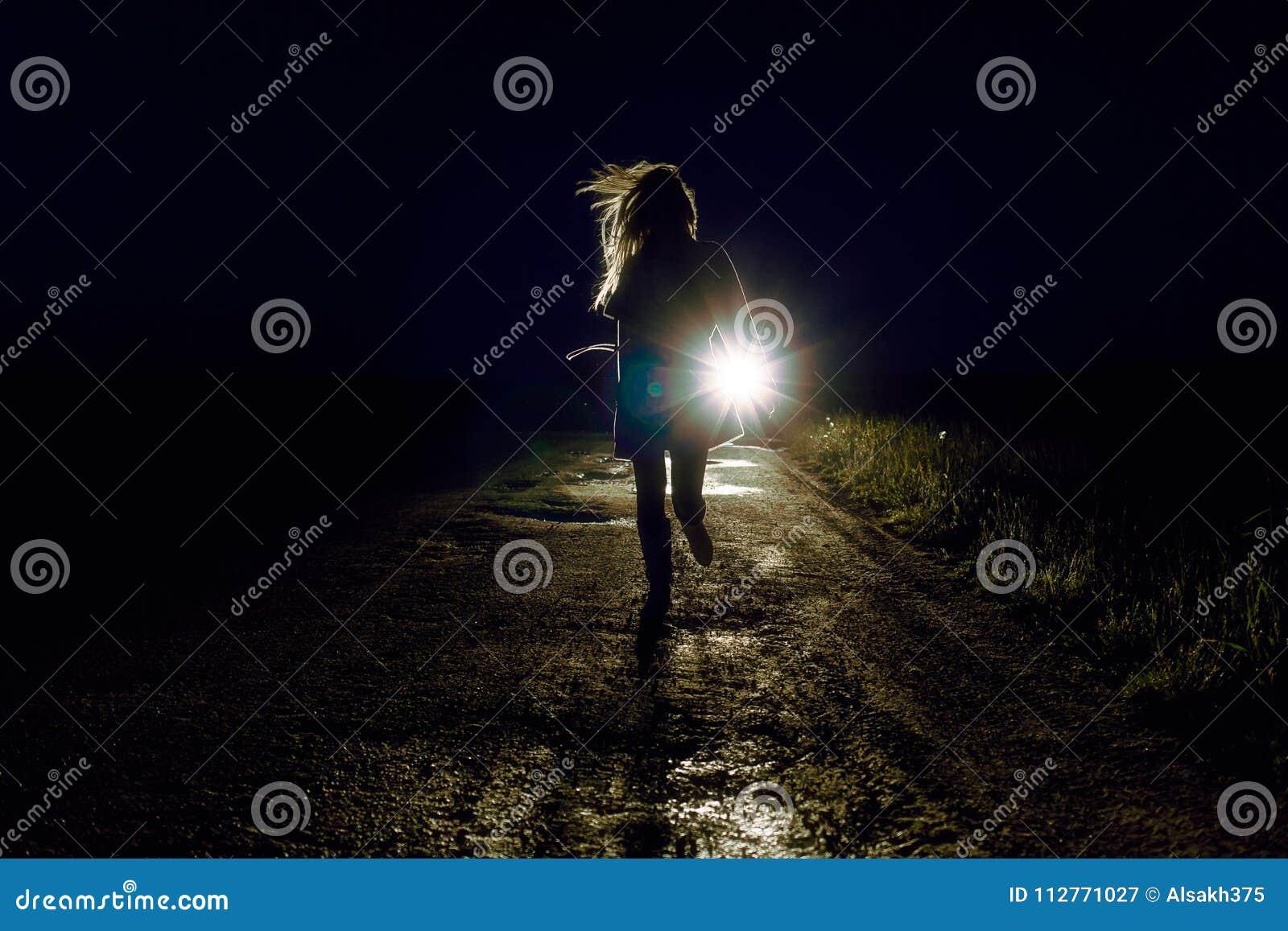 在运行远离追求者的夜乡下公路的女性剪影乘汽车根据车灯