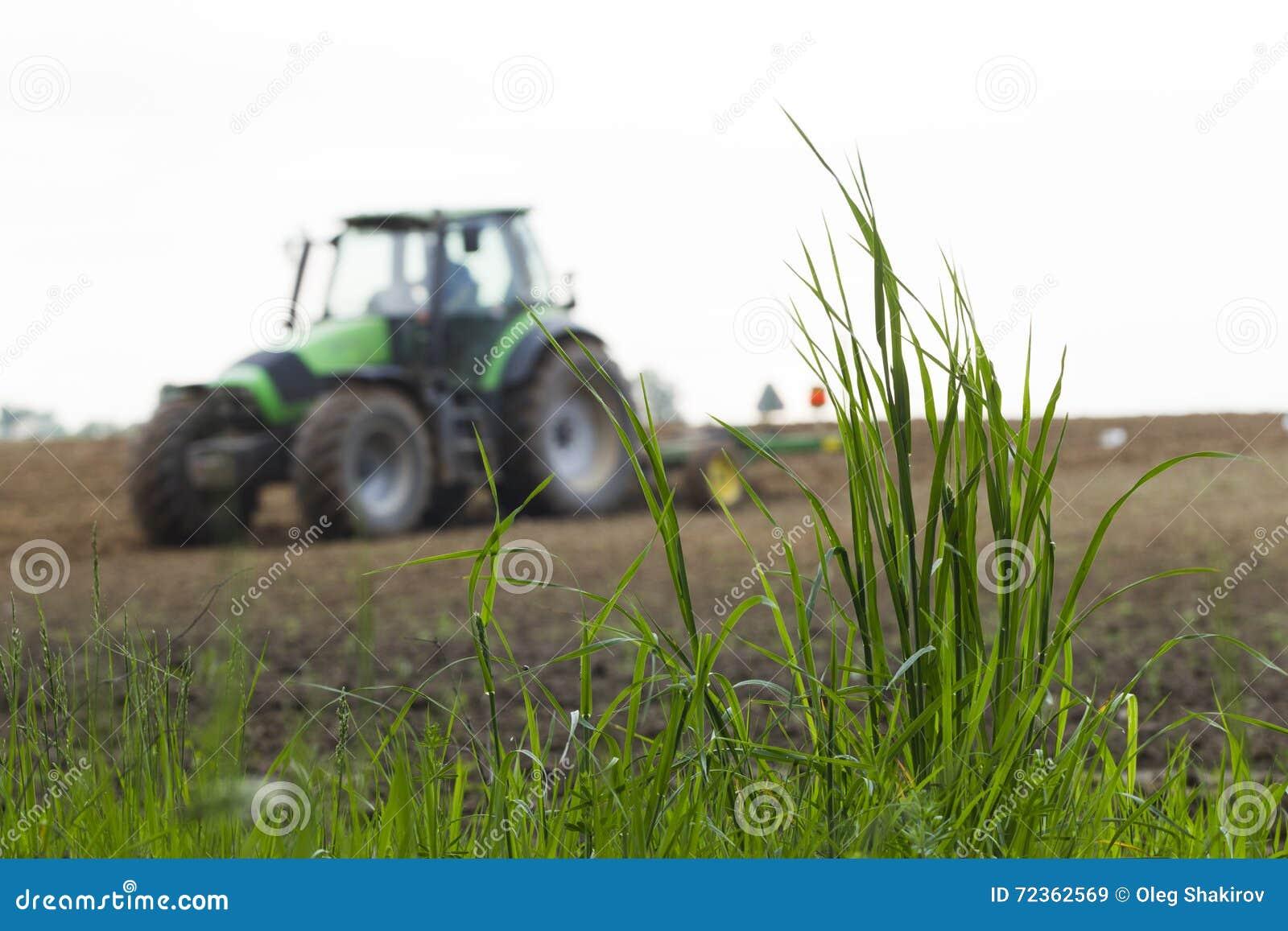 在运转的拖拉机背景的绿草
