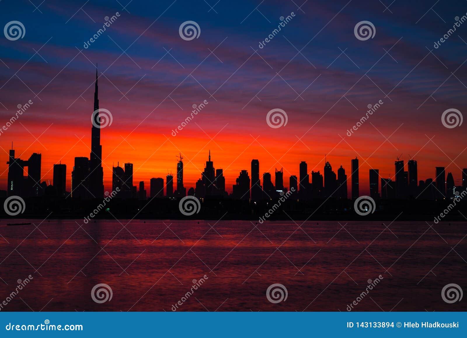 在迪拜的神话血淋淋的红色天空 黎明、早晨、日出或者黄昏在哈里发塔 美丽的色的多云天空