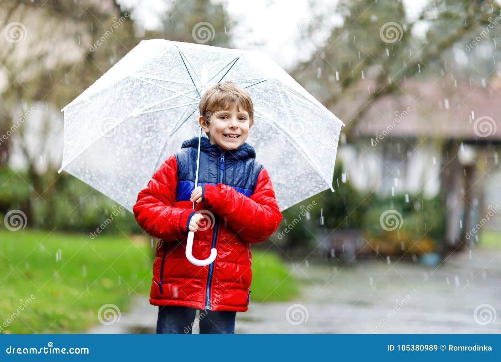 在途中的小白肤金发的孩子男孩对学校走在雨夹雪、雨和雪期间的与一把伞在冷的天