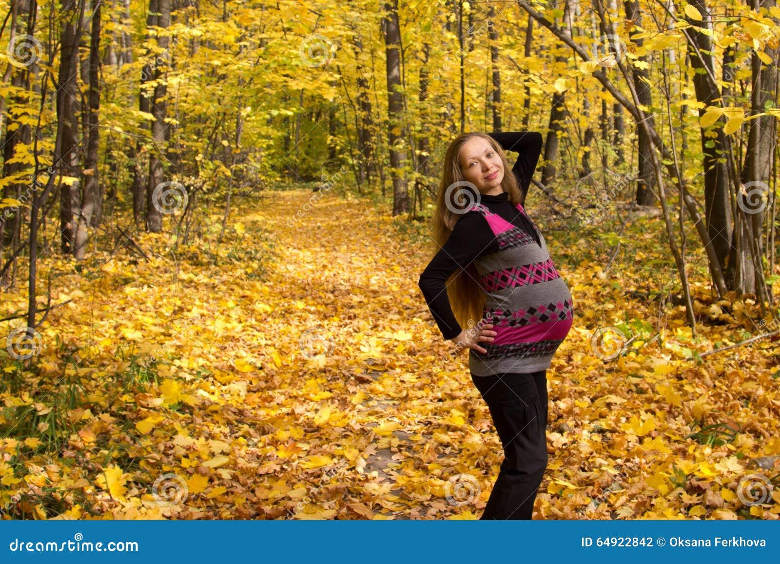 妊妇先锋影�_走在金黄秋天森林妊妇,一名妇女在第九个月怀孕.