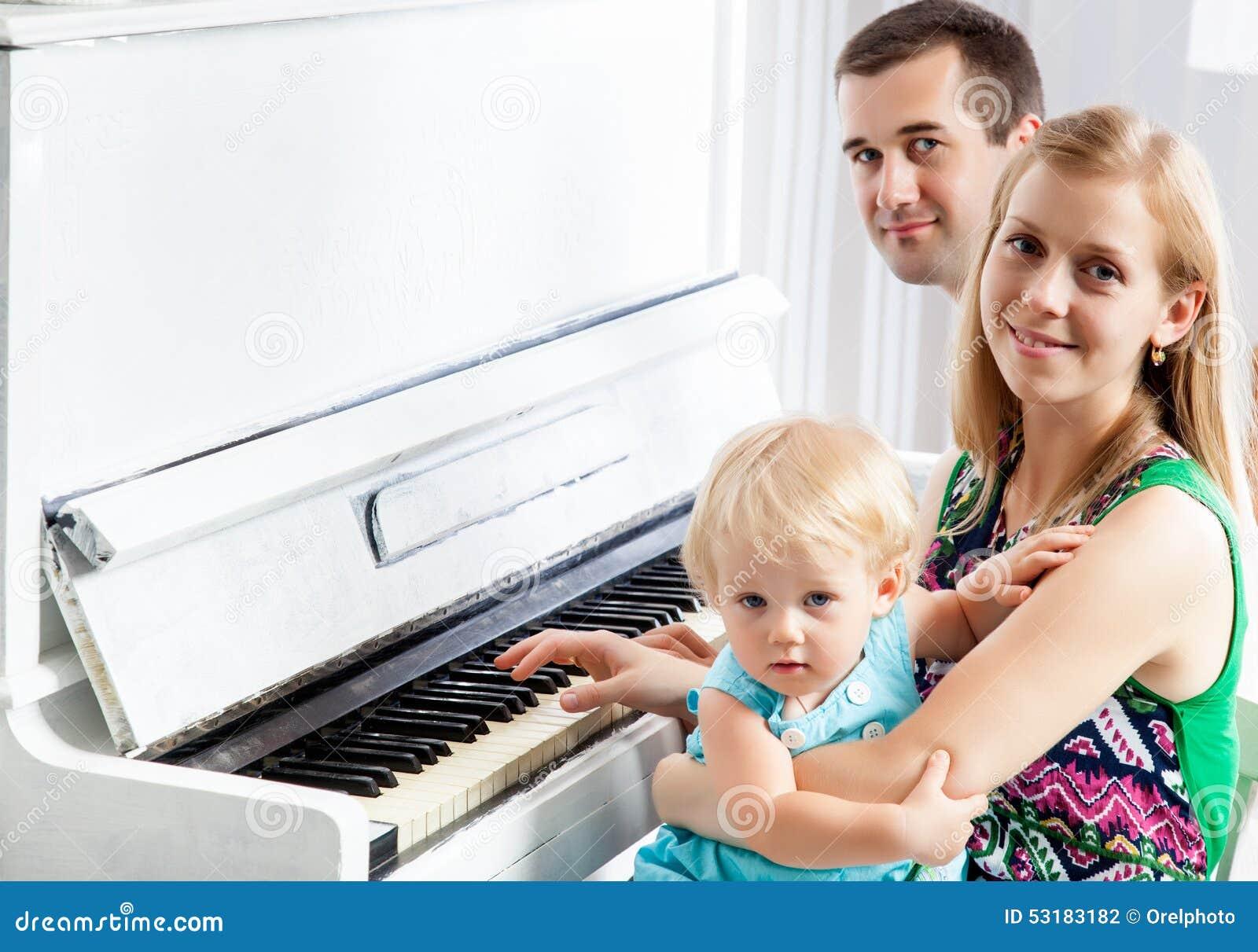 在钢琴附近的愉快的家庭