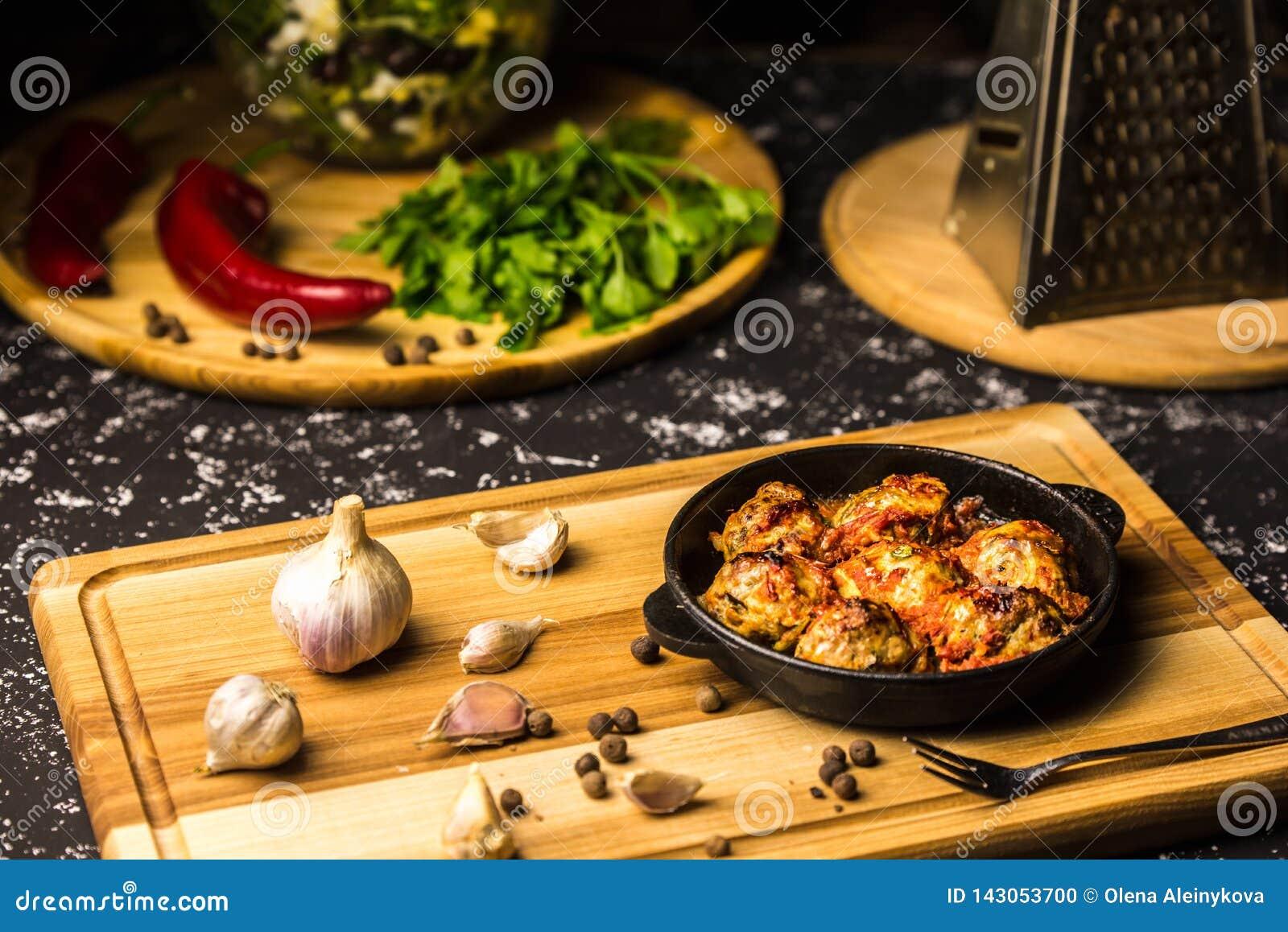 在铁平底锅的丸子在一个木板用大蒜和干胡椒