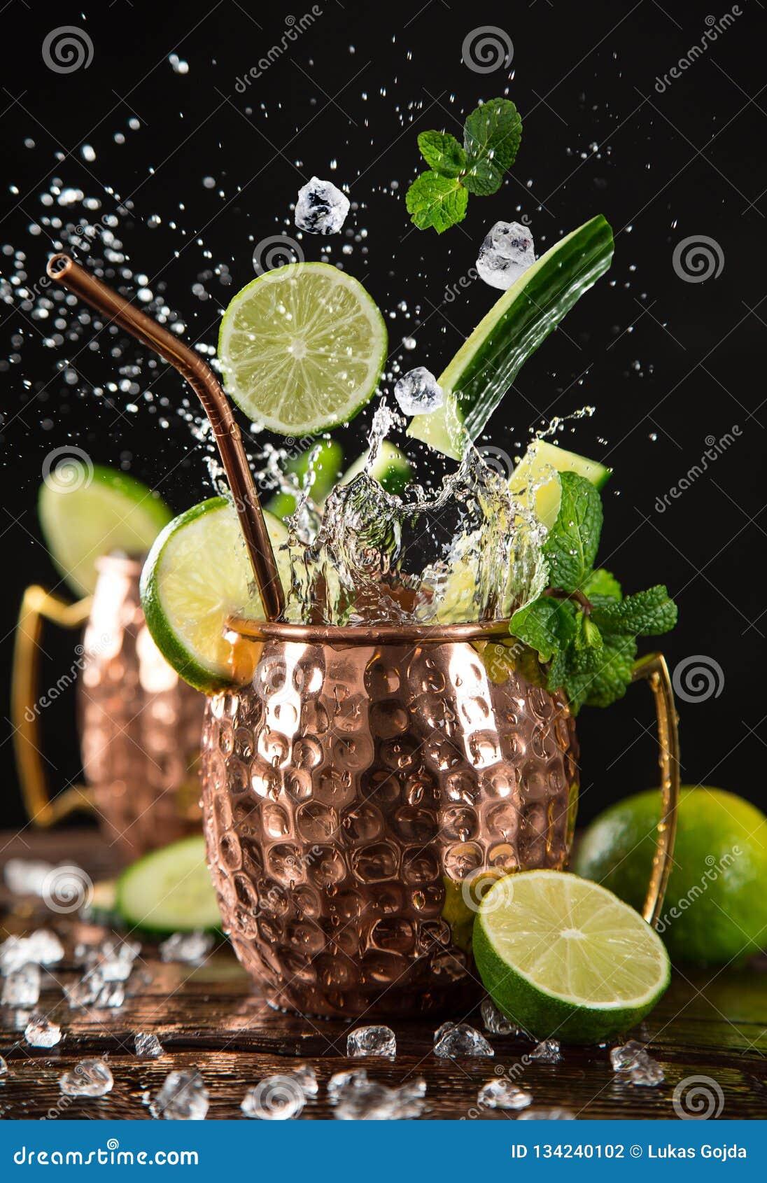 在铜杯子的著名飞溅的莫斯科骡子酒精鸡尾酒