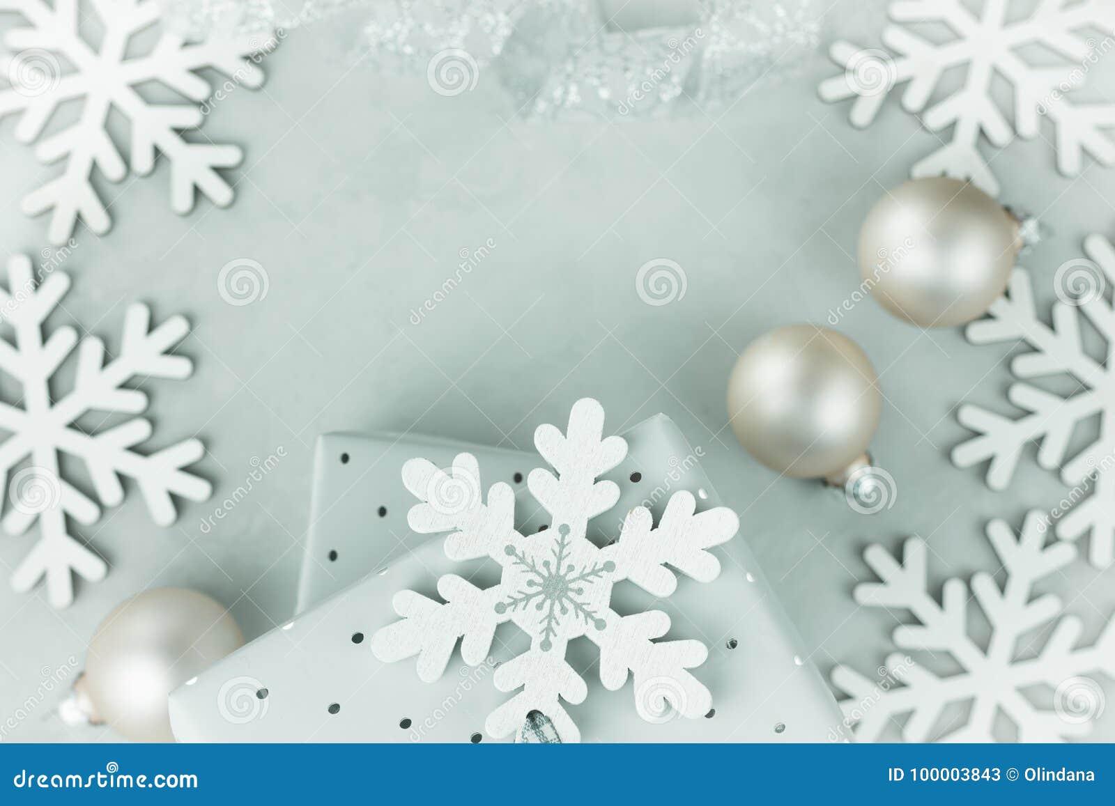 在锡箔包裹的礼物盒 卷曲的银色丝带 圣诞节中看不中用的物品,雪剥落在框架安排了 复制文本的空间