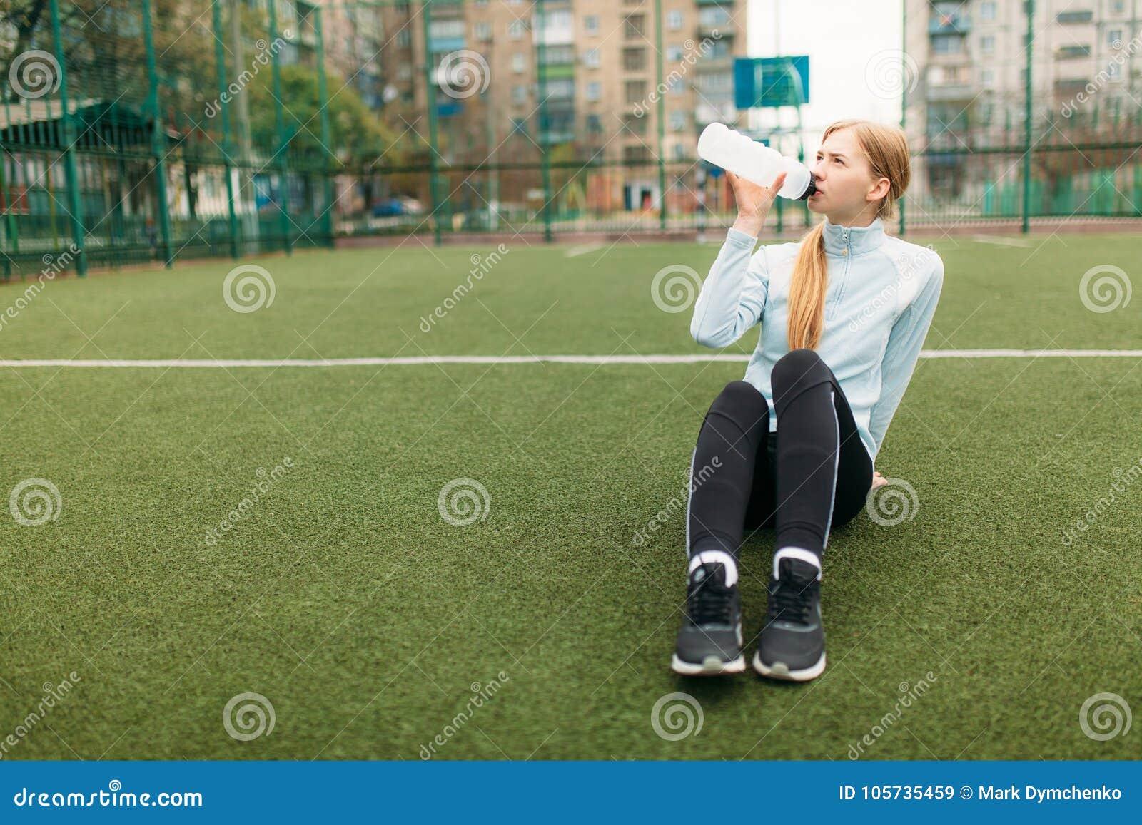在锻炼以后的女孩,在橄榄球场的饮用水 美丽的女孩画象运动服的