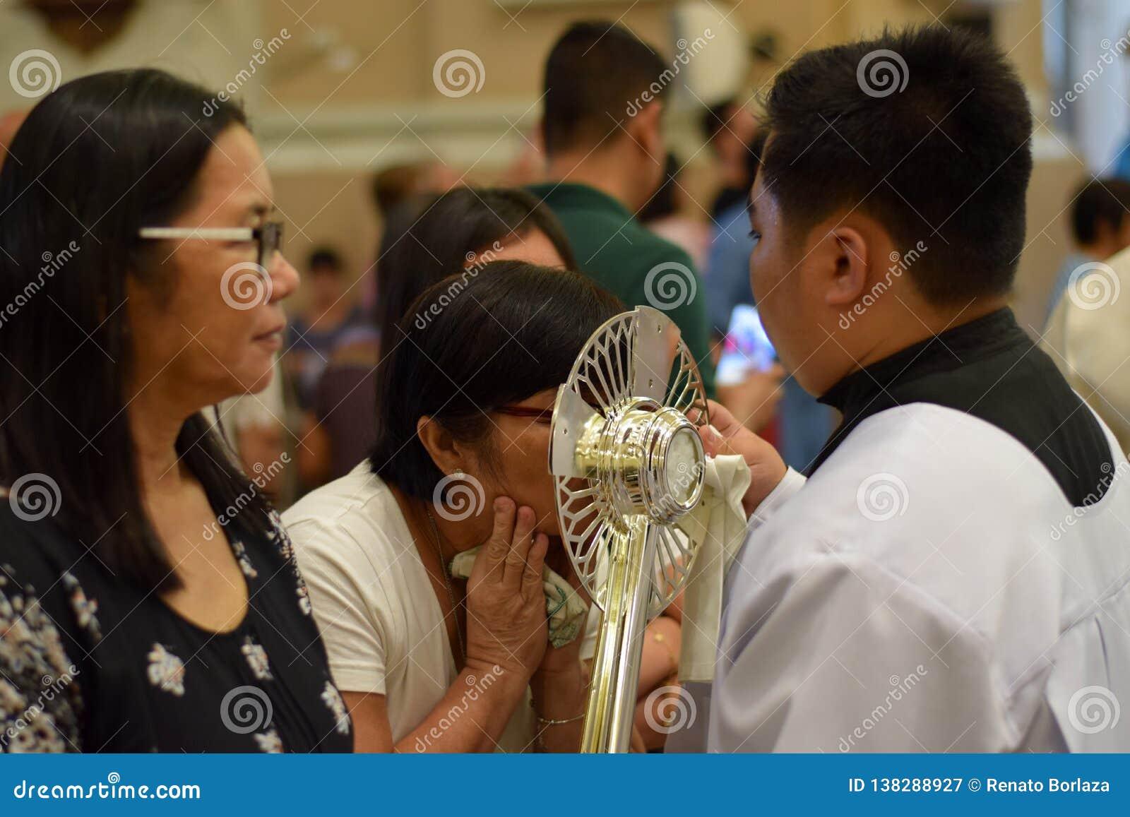 在镇庆祝期间,天主教妇女给亲吻的圣洁圣体匣的罕见的机会