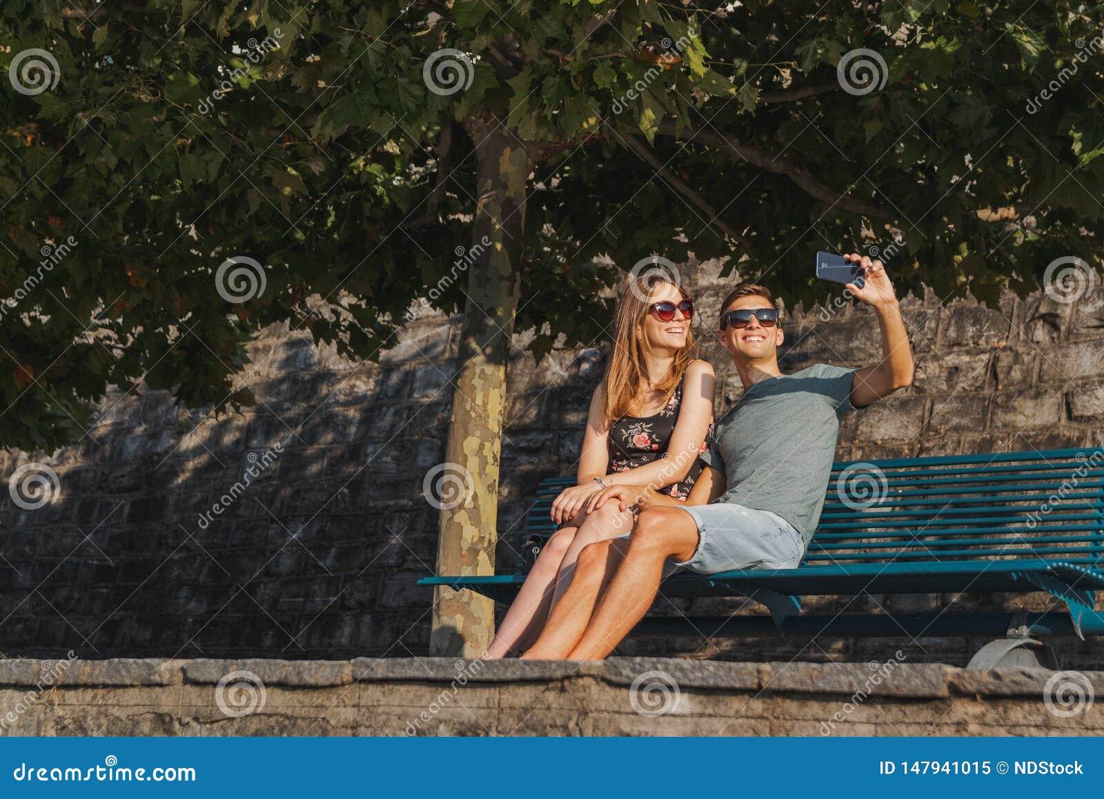 在长凳在爱的年轻夫妇供以座位的采取selfie和放松在一好日子期间