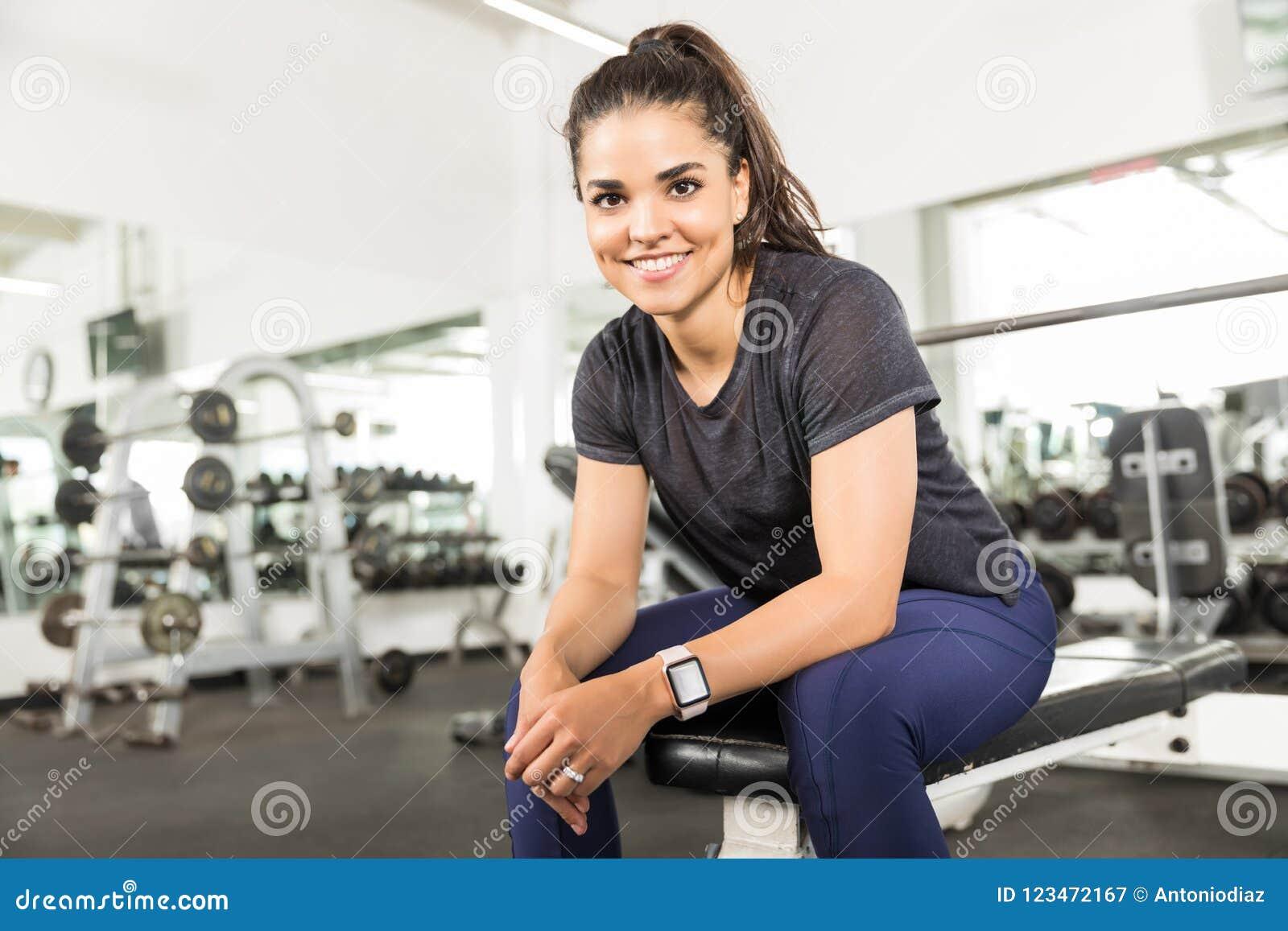 在长凳的微笑的健康女性开会在健身中心