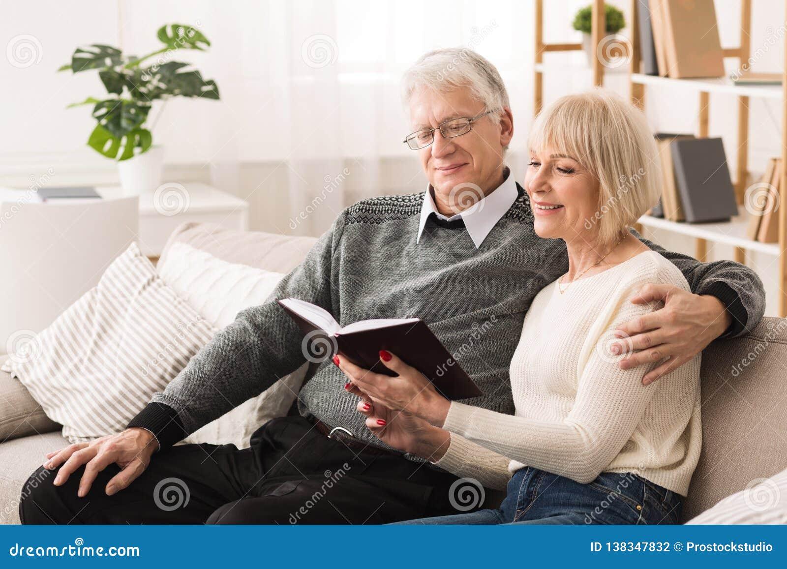 在长沙发的愉快的老夫妇看书在家