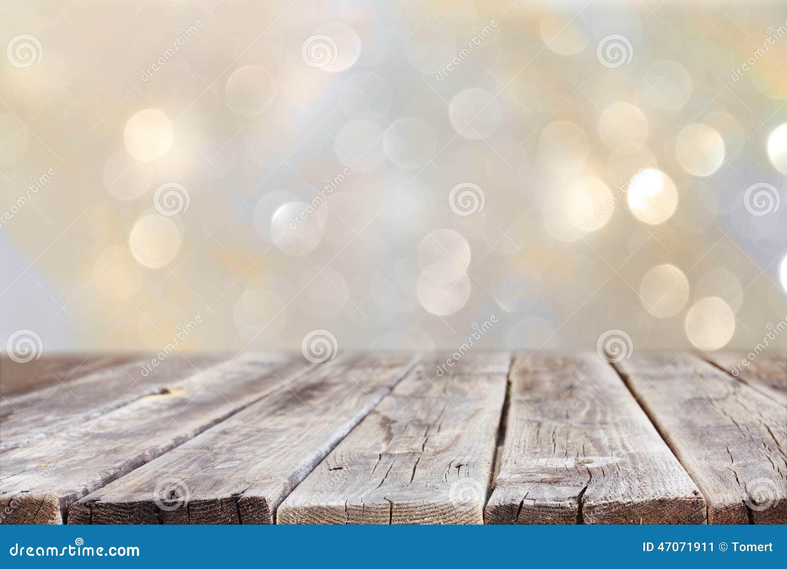 在闪烁银和金明亮的bokeh光前面的土气木桌