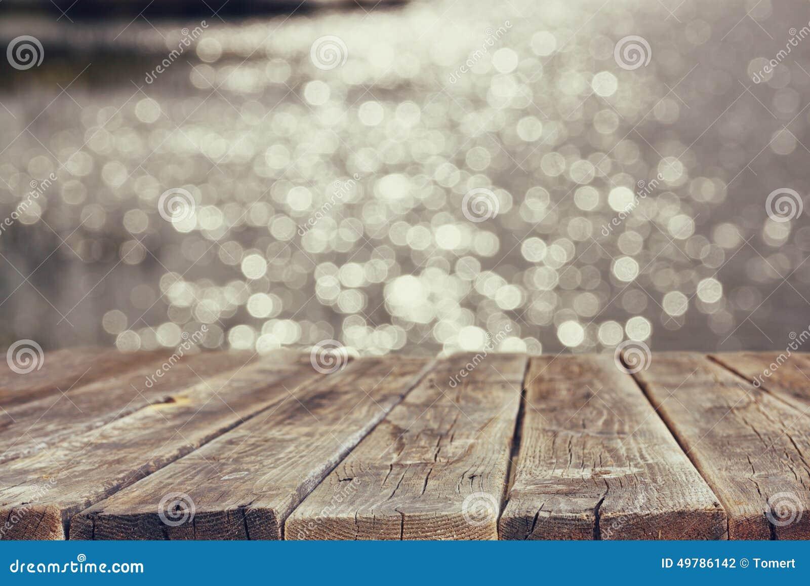 在闪耀的湖水前面夏天风景的木委员会桌  背景被弄脏