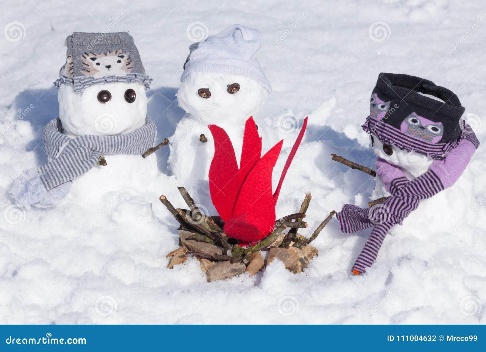 在阵营火附近的三个逗人喜爱的雪人