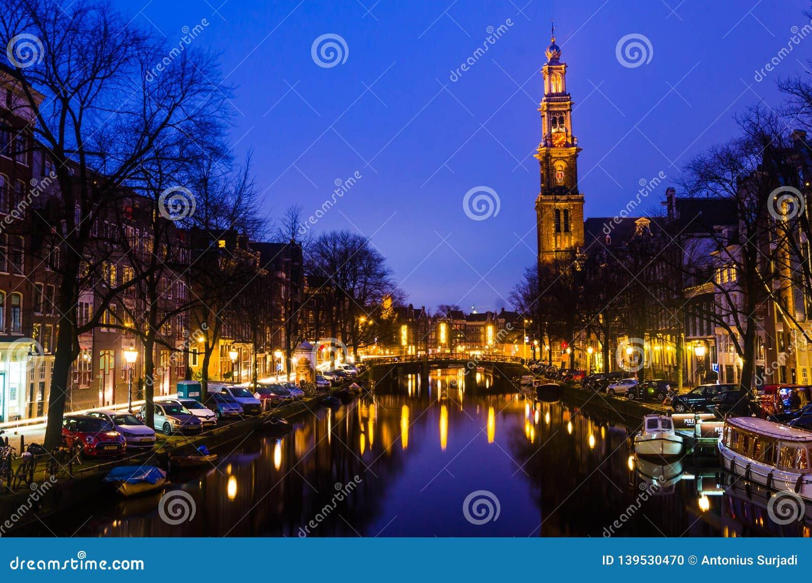 在阿姆斯特丹运河的早晨蓝色日出有在背景天际的教堂钟塔的