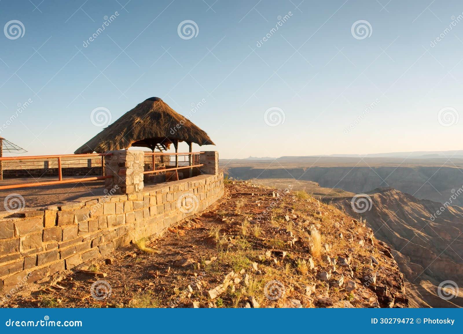 在陡峭旁边的茅草屋顶风雨棚-日落