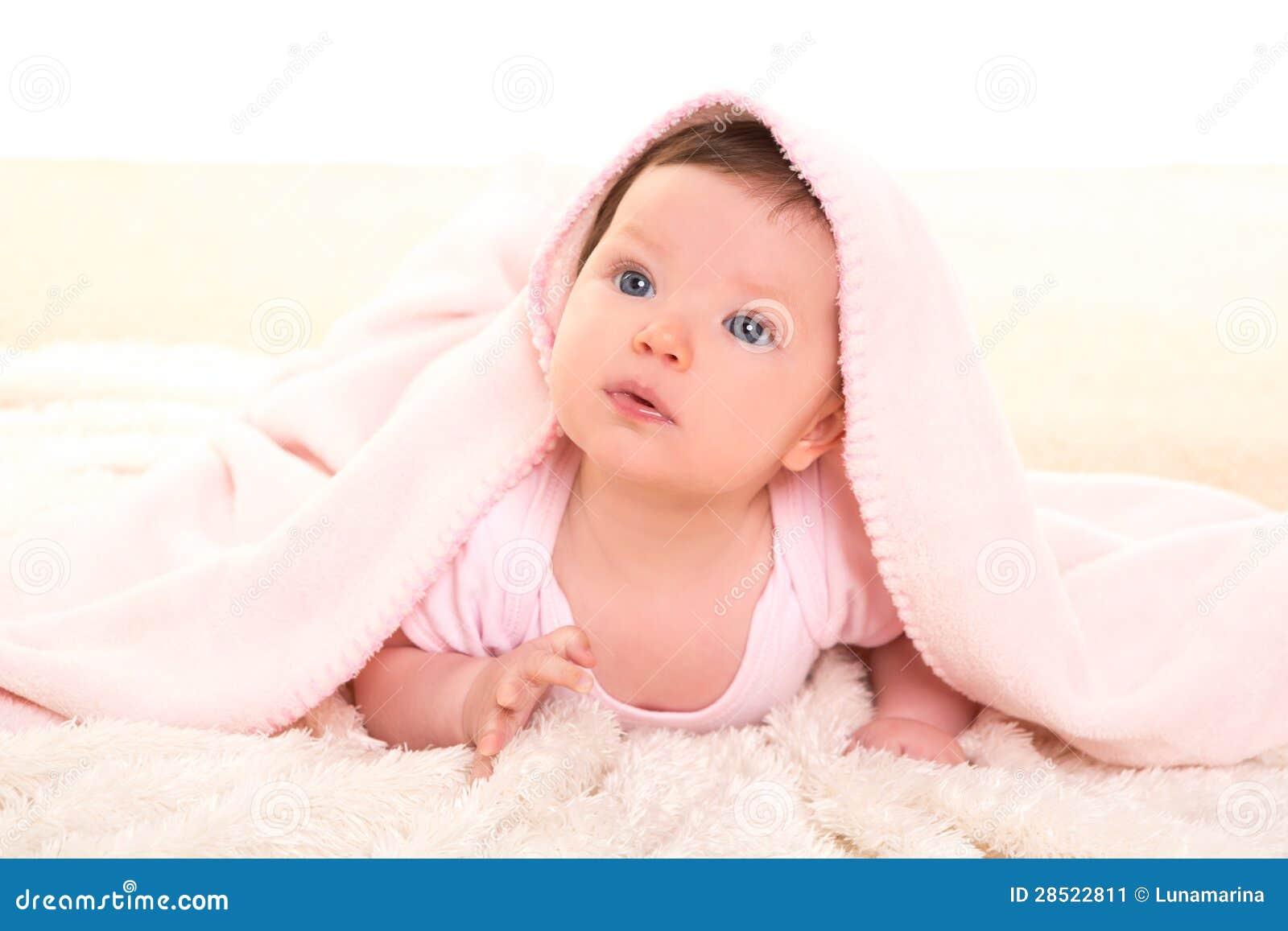 在隐藏的桃红色毯子之下的女婴在空白毛皮