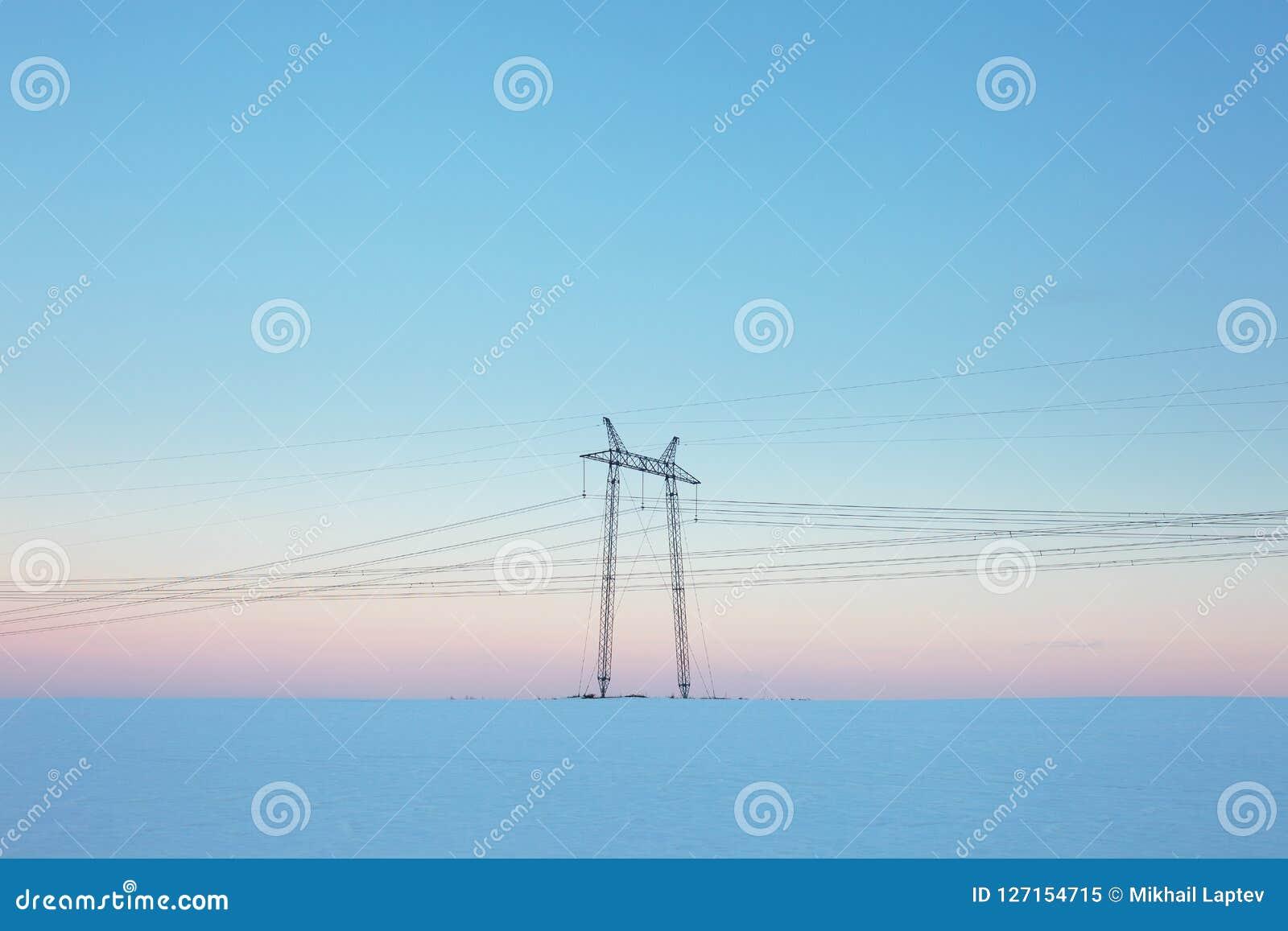 在雪原的输电线在淡色日落
