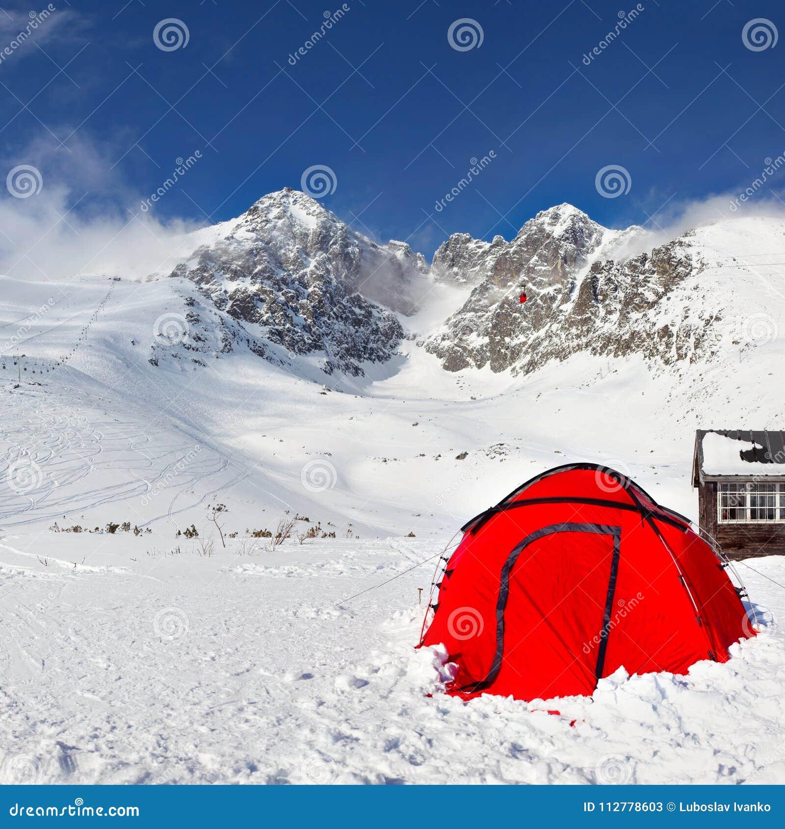 在雪的明亮的红色上升的帐篷