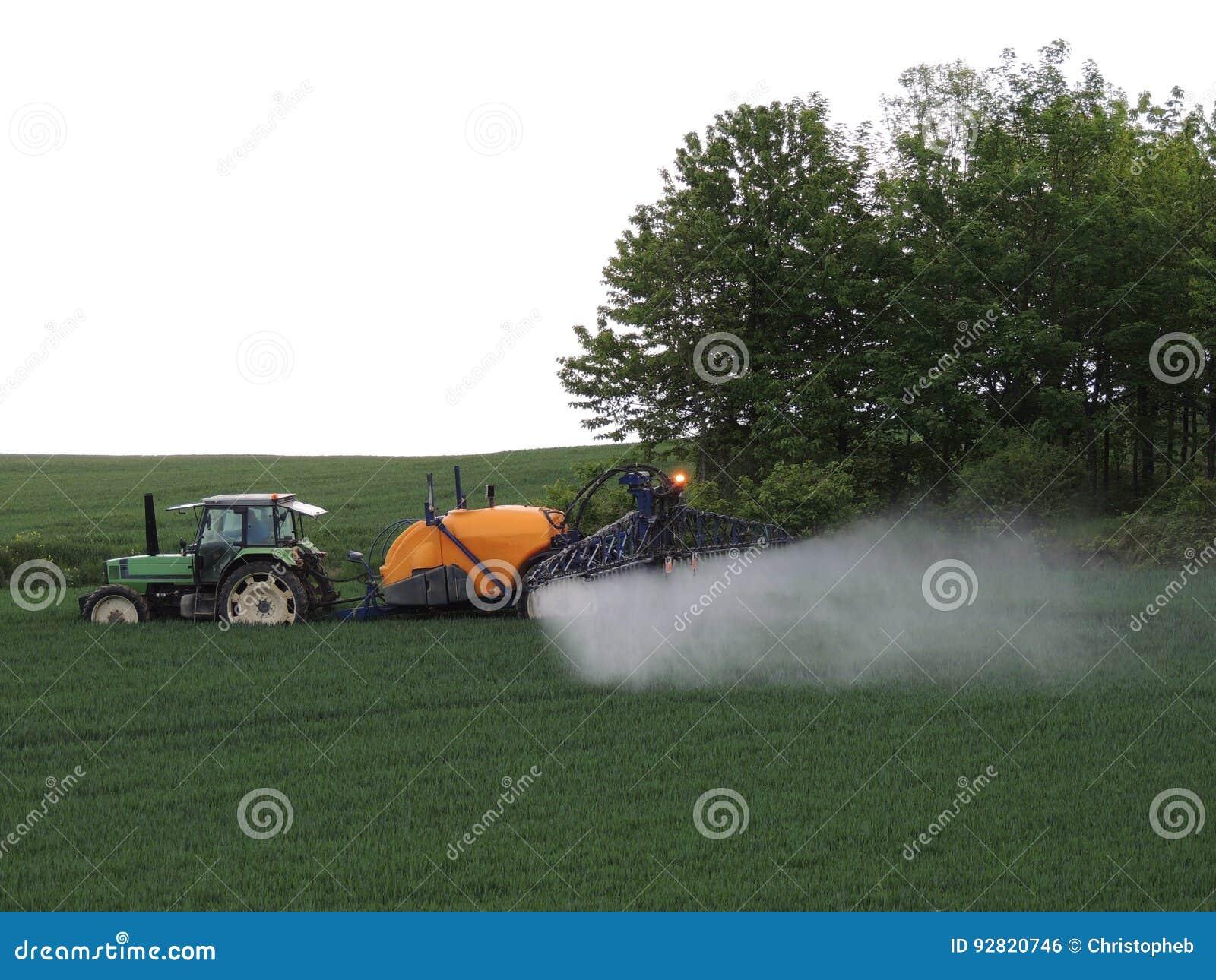 在领域的农夫喷洒的化学制品