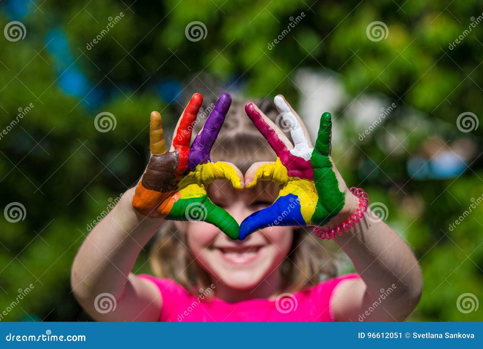 在颜色油漆的孩子手做心脏形状,在手上的焦点