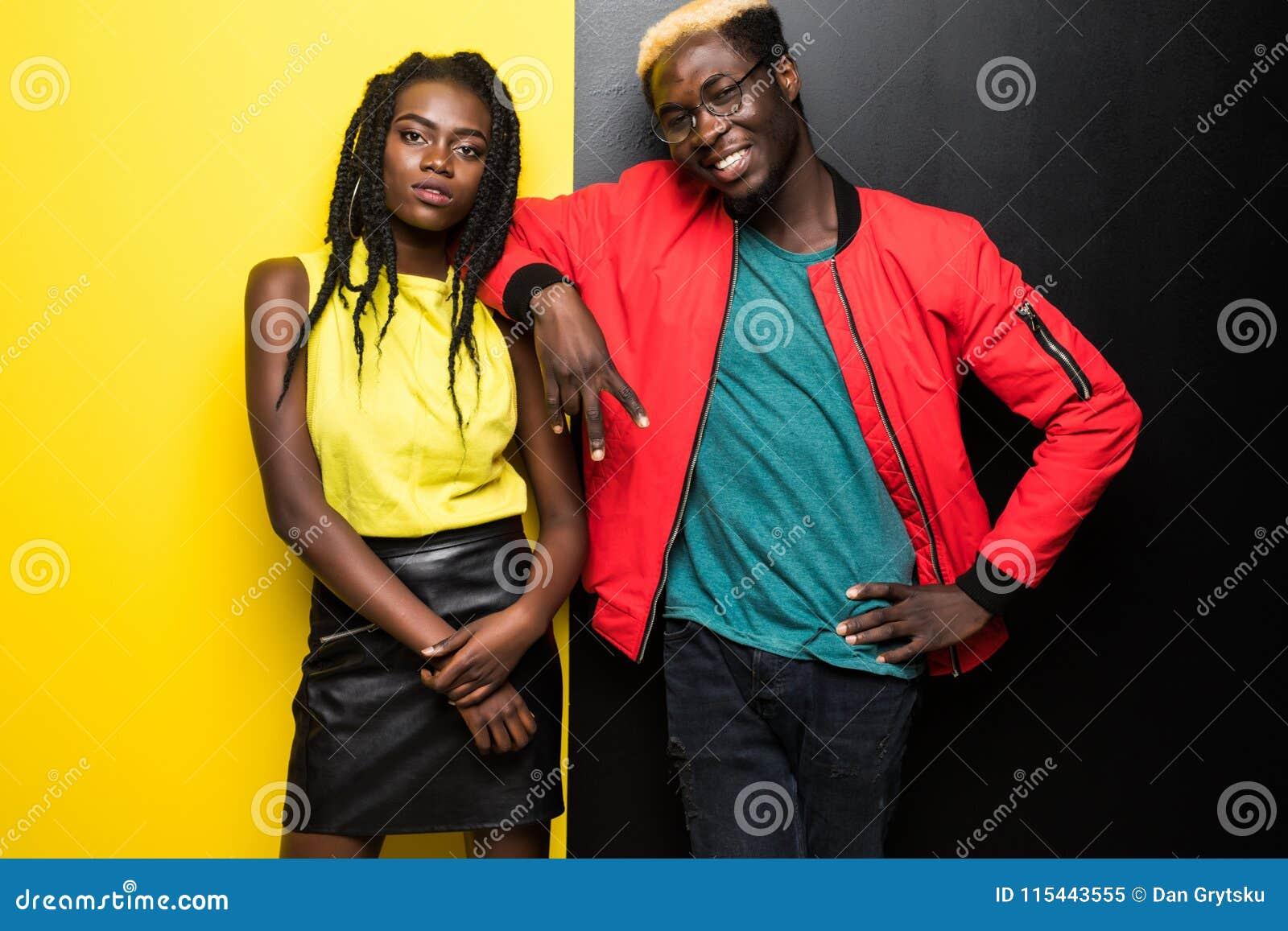 在颜色背景隔绝的年轻和愉快的美国黑人的夫妇 在黄色和bla获得乐趣隔绝的男人和妇女美国黑人