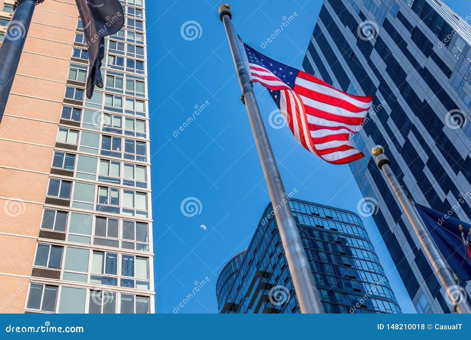 在风的美国国旗波浪,在摩天大楼中在街市布鲁克林,NY,美国