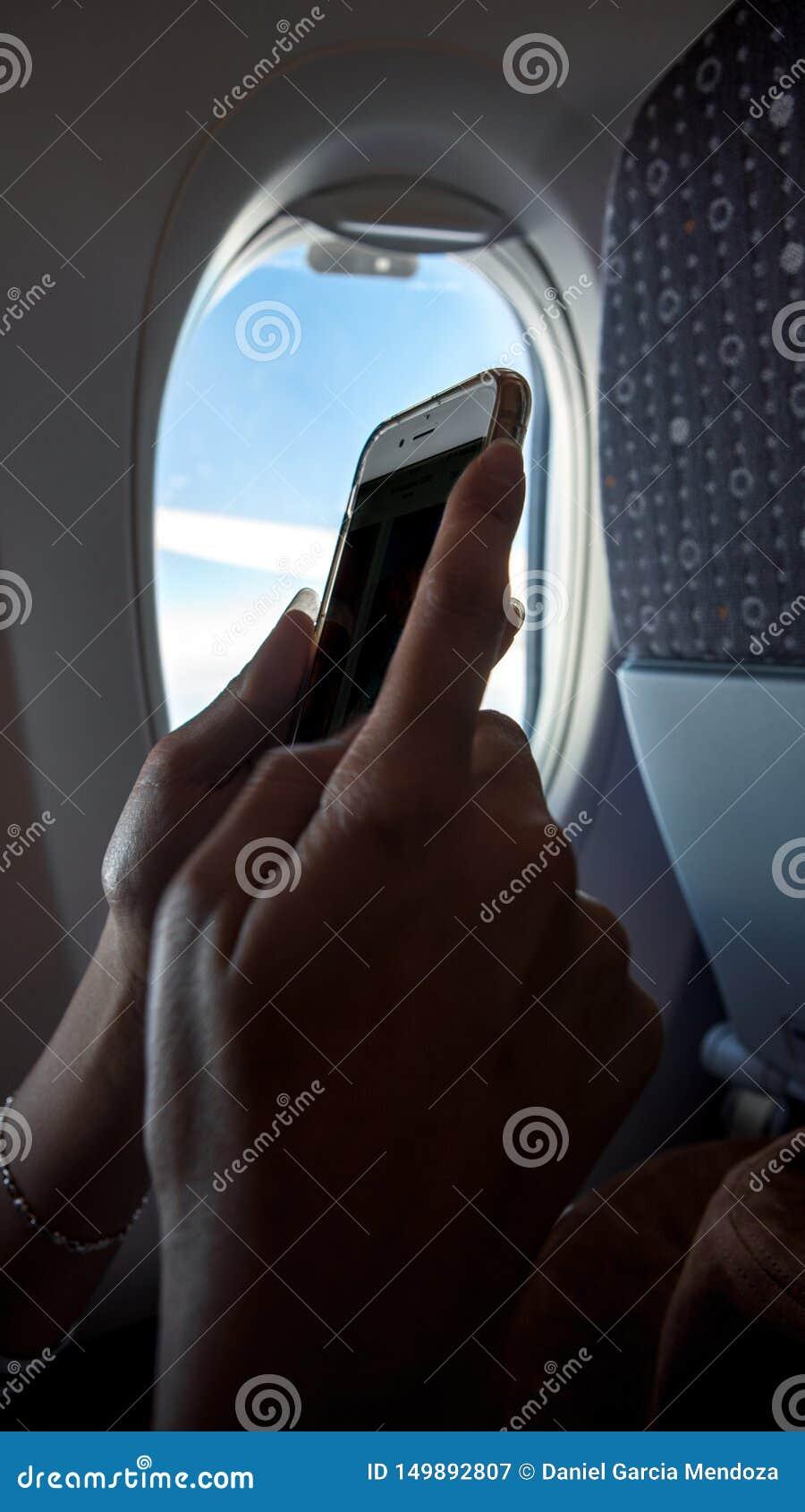 在飞行旅行期间的亚洲妇女藏品智能手机 在飞机上的旅行家