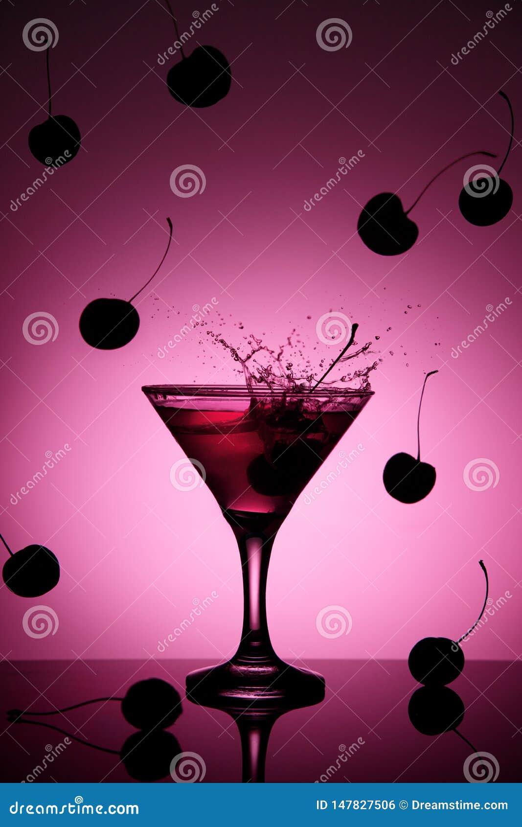 在马蒂尼鸡尾酒玻璃与飞溅和落的樱桃的桃红色樱桃coctail在背景
