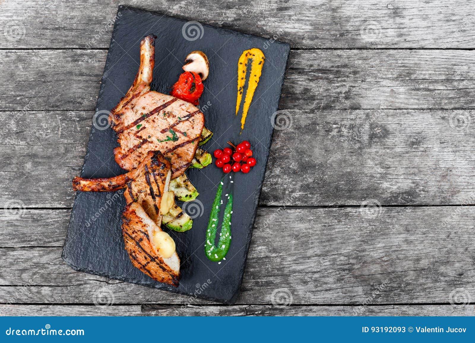 在骨头的烤猪肉牛排充塞用乳酪、烤菜和莓果在石板岩背景在木背景