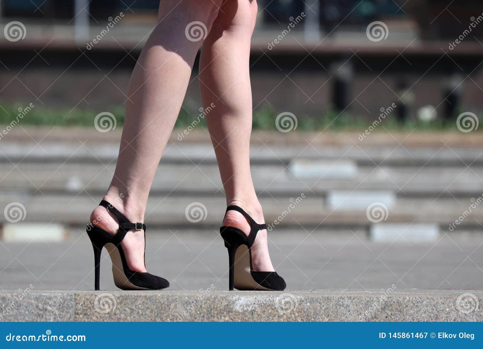 在高跟鞋,站立在街道上的凉鞋的亭亭玉立的妇女的性感的女性腿
