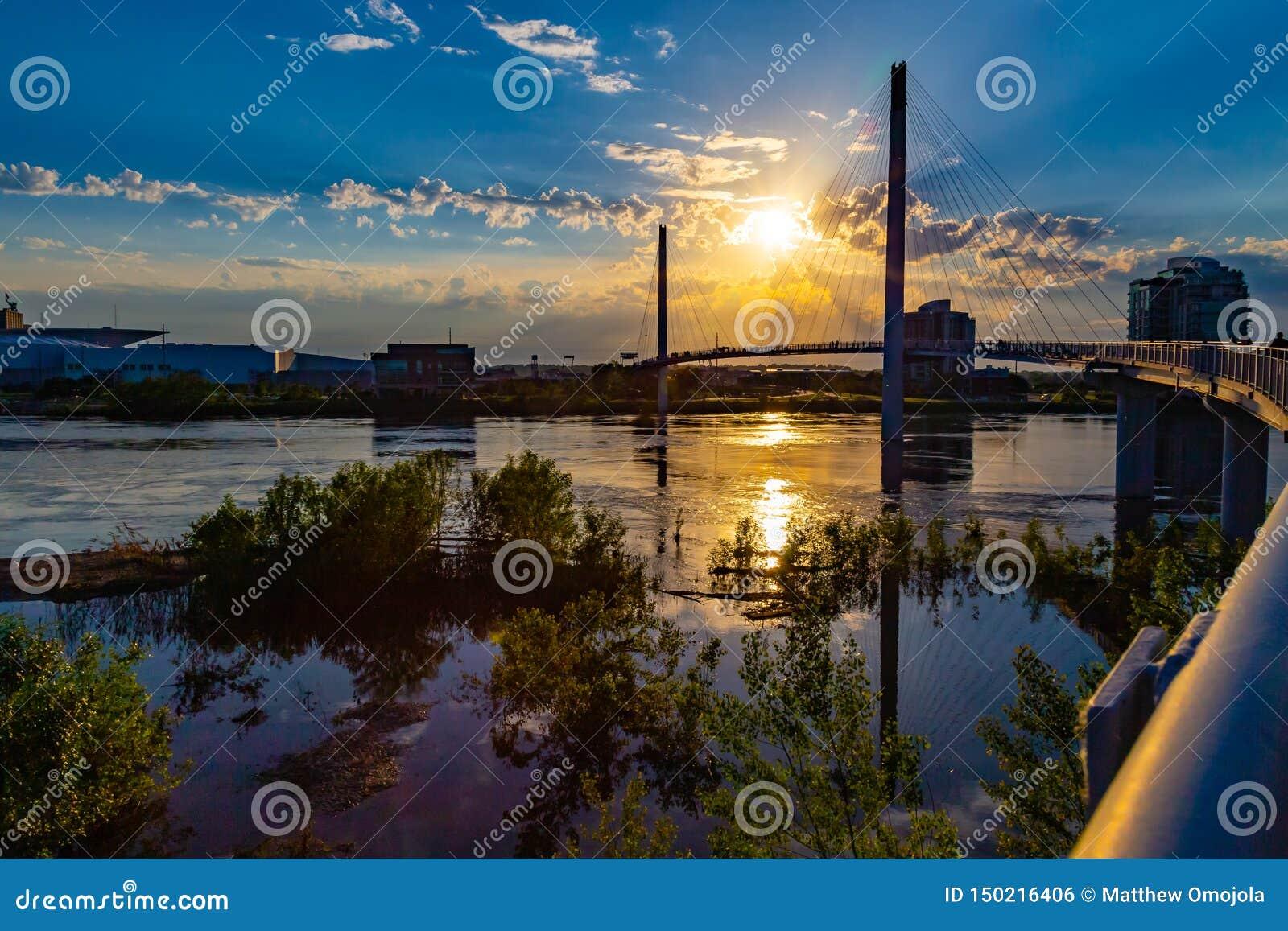 在鲍伯克里步行桥的日落和奥马哈河边区的圆鼓的密苏里河