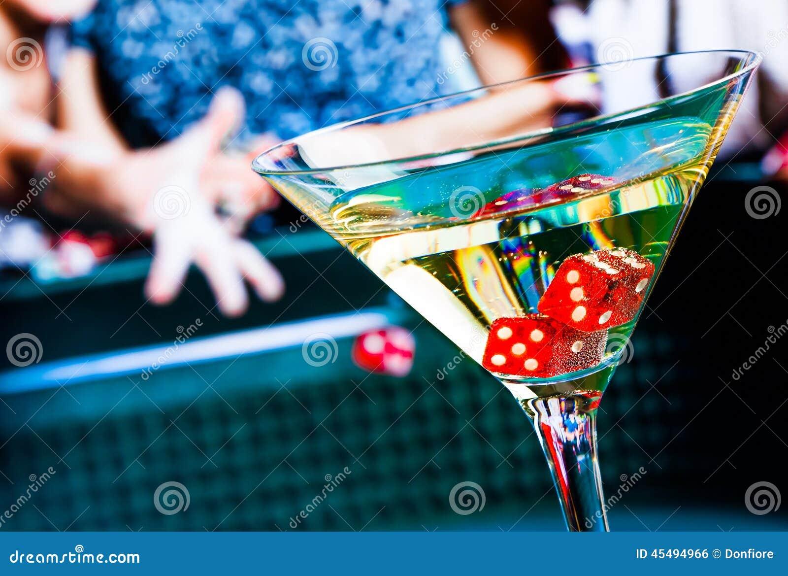 在鸡尾酒杯的红色模子在赌博的桌前面