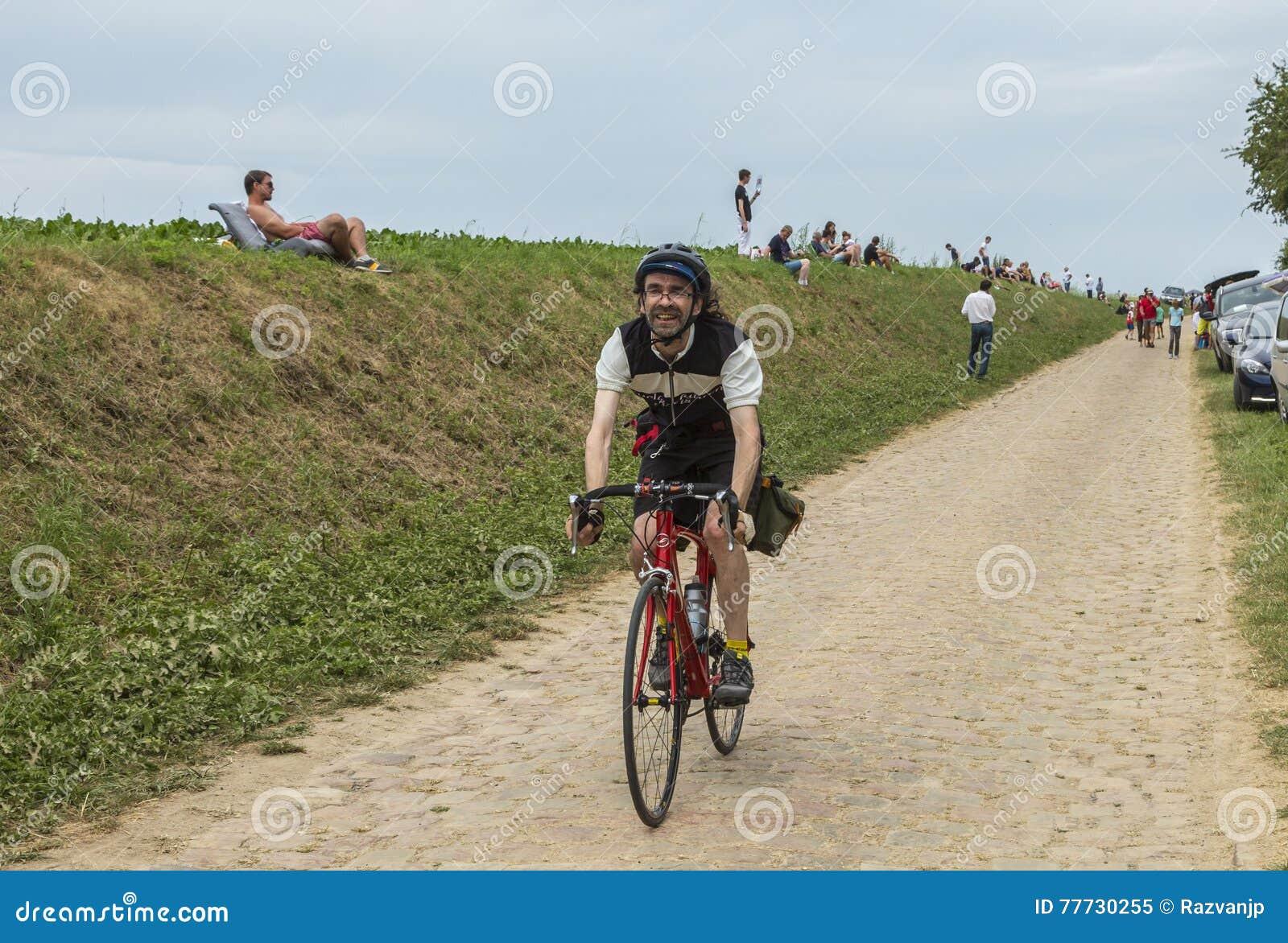 在鹅卵石路的非职业骑自行车者骑马-环法自行车赛20